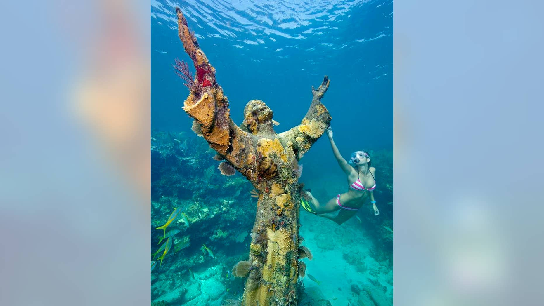 """Katherine Wieland snorkels by the """"Christ of the Abyss"""" statue, an underwater icon for John Pennekamp Coral Reef State park, off Key Largo, Fla. Named after a former Miami newspaper editor, Pennekamp is the nation's first underwater preserve."""