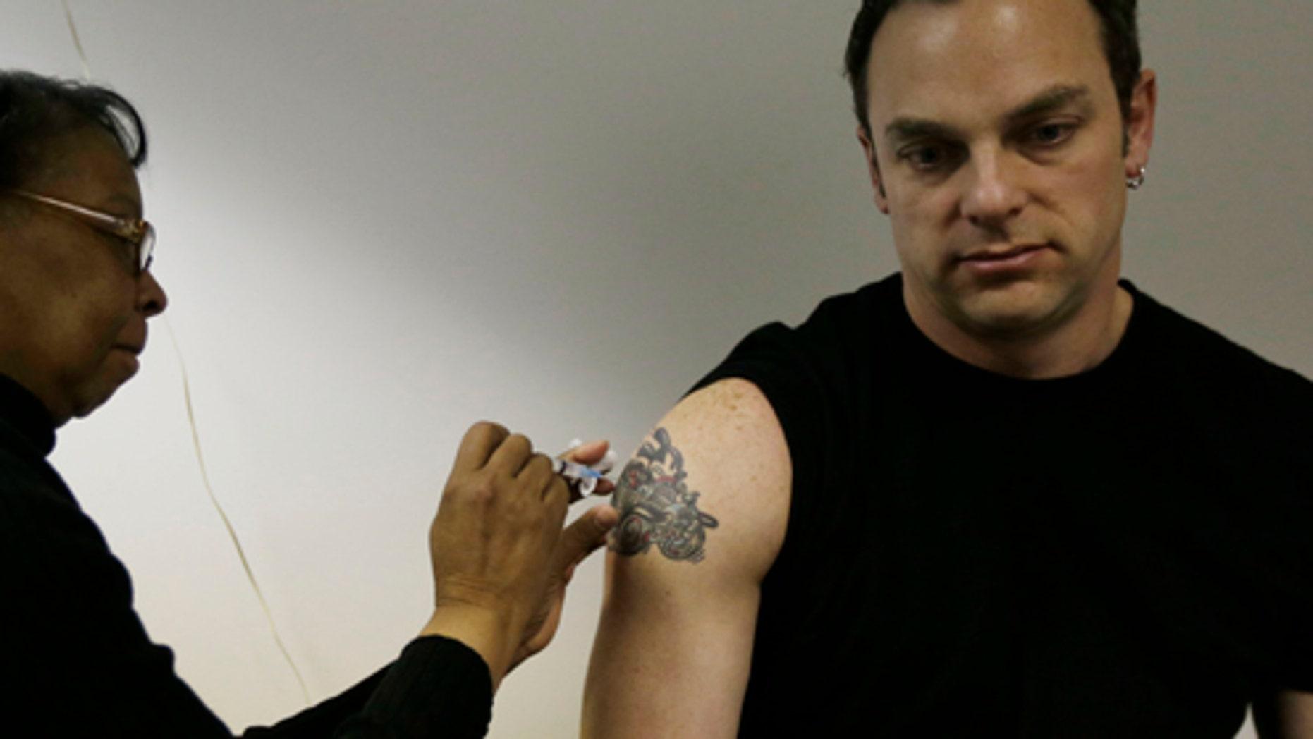 Pam Horn administers the flu vaccine to employee Michael Karolitzky at Philly Flu Shots on Thursday, Jan. 10, 2013, in Philadelphia. (AP Photo/Matt Rourke)