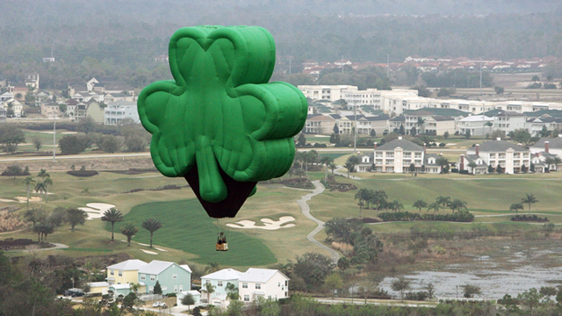 "A green shamrock hot-air balloon, named ""Paddy"" and flown by Orlando Balloon Rides, drifts over Florida on St. Patrick's Day."
