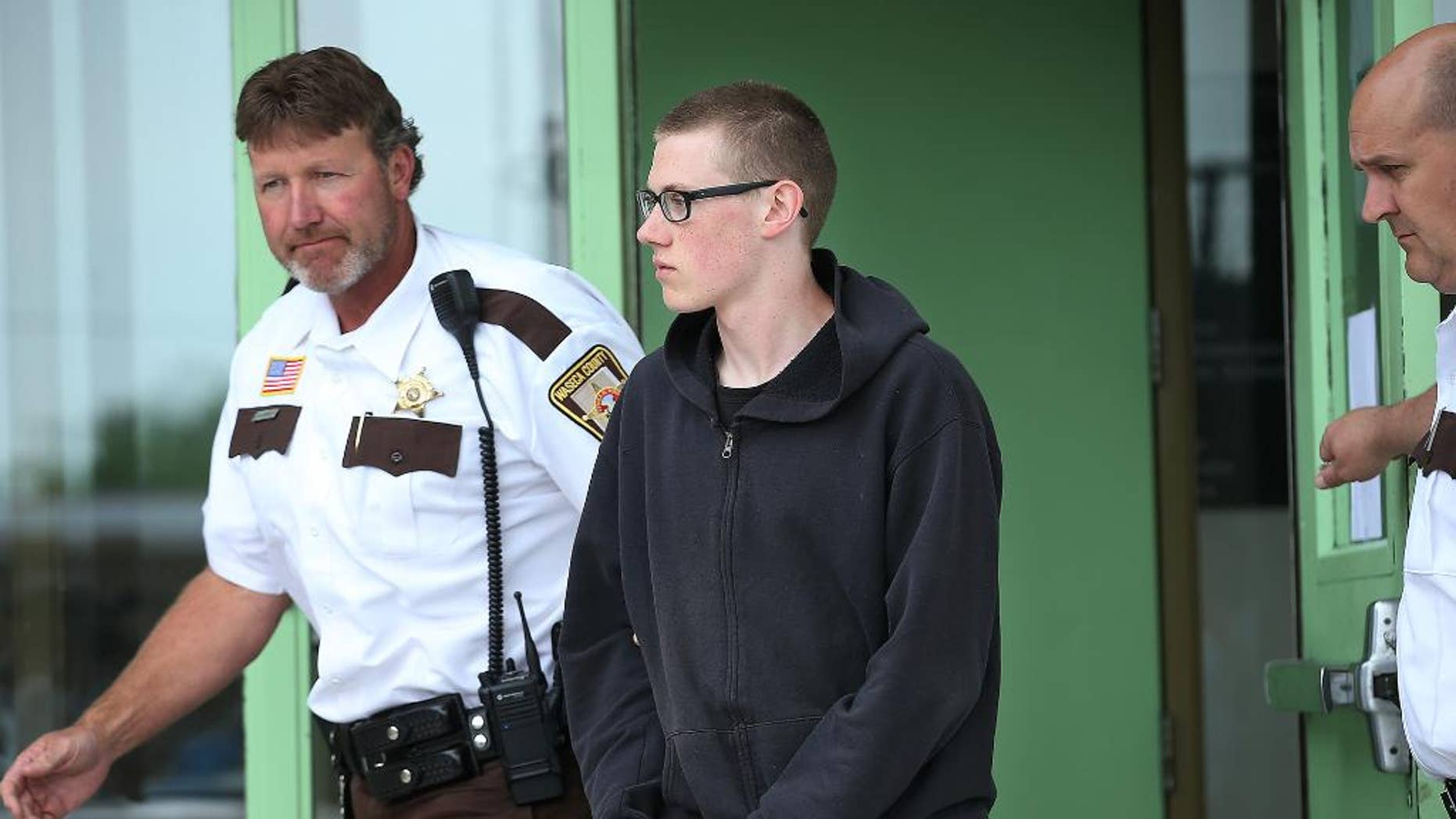 In this photo taken June 30, 2014, John LaDue, accused of planning an attack on his school, is escorted by Waseca County Sheriff's  Deputies for a hearing in Waseca, Minn. District Judge Robert Birnbaum on Friday, Aug. 21, 2015, has certified the Waseca teenager, accused of planning to kill his family and attack his high school, to stand trial as an adult. (Elizabeth Flores/Star Tribune via AP)  MANDATORY CREDIT; ST. PAUL PIONEER PRESS OUT; MAGS OUT; TWIN CITIES LOCAL TELEVISION OUT