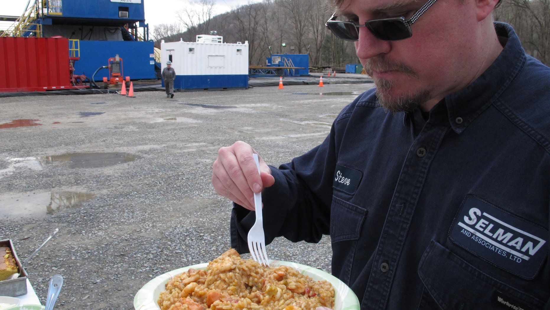 Geologist Steve Clark prepares to take a bite of jambalaya prepared for workers on a natural gas drilling site near Montoursville, Pa.