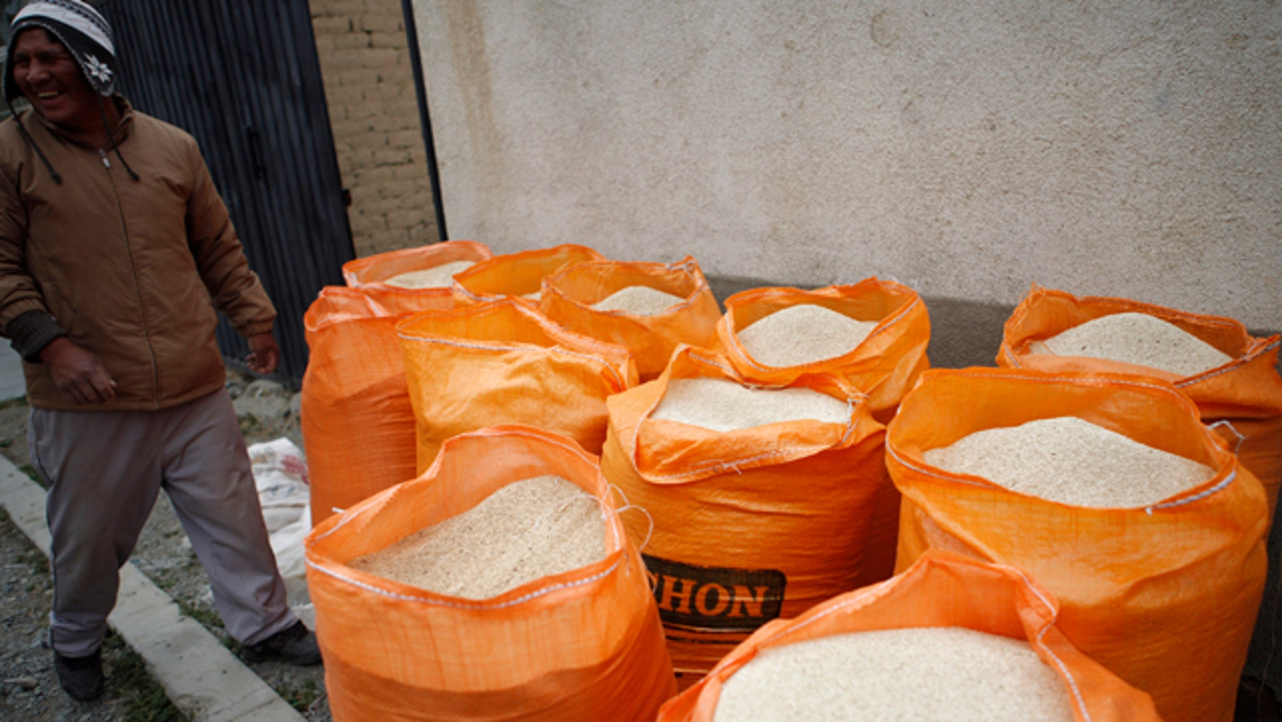 In this photo taken Oct. 2, 2010, a man stands next to bags filled with quinoa grain in La Paz, Bolivia. Quinoa's rising popularity among First World foodies has been a boon to some of the poor farmers in the semiarid highlands of Bolivia.   (AP Photo/Juan Karita)