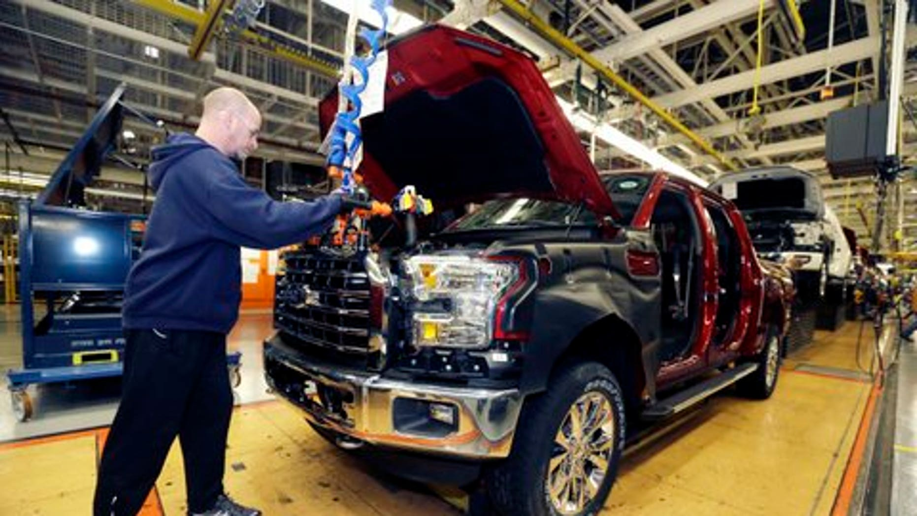In this Nov. 6, 2014 photo, Chris Lucking installs a grill on a new Ford F-150 truck at the Dearborn Truck Plant in Dearborn, Mich. Itís Ford Motor Co.ís biggest bet in decades: an aluminum-sided F-150 that could set a new industry standard _ or cost the company its pickup truck crown. (AP Photo/Carlos Osorio)
