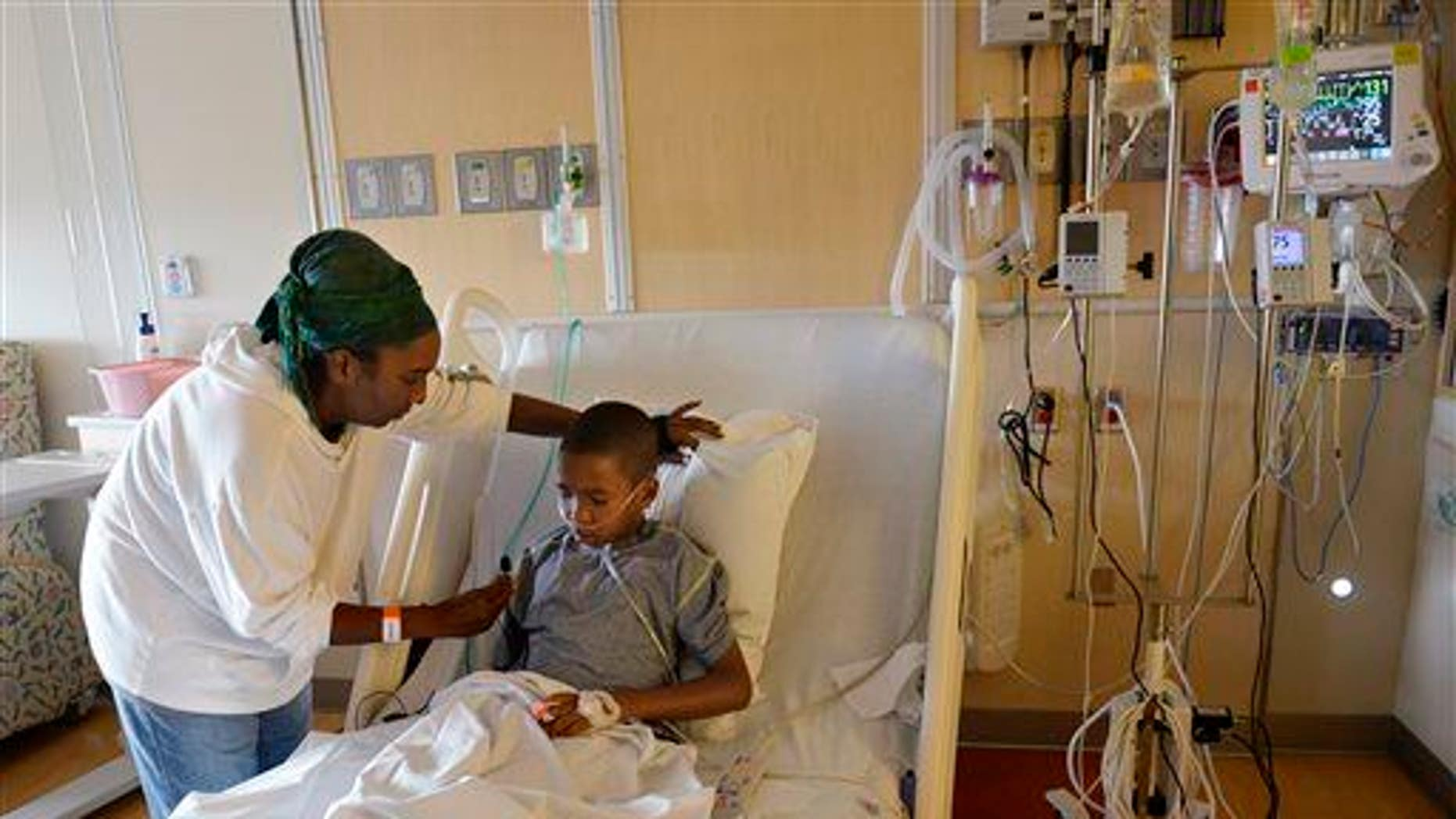 In this Sept. 8, 2014, photo, Melissa Lewis of Denver helps her son, Jayden Broadway, 9, as he coughs in his bed at the Children's Hospital Colorado in Aurora, Colo. He was treated for enterovirus-68.