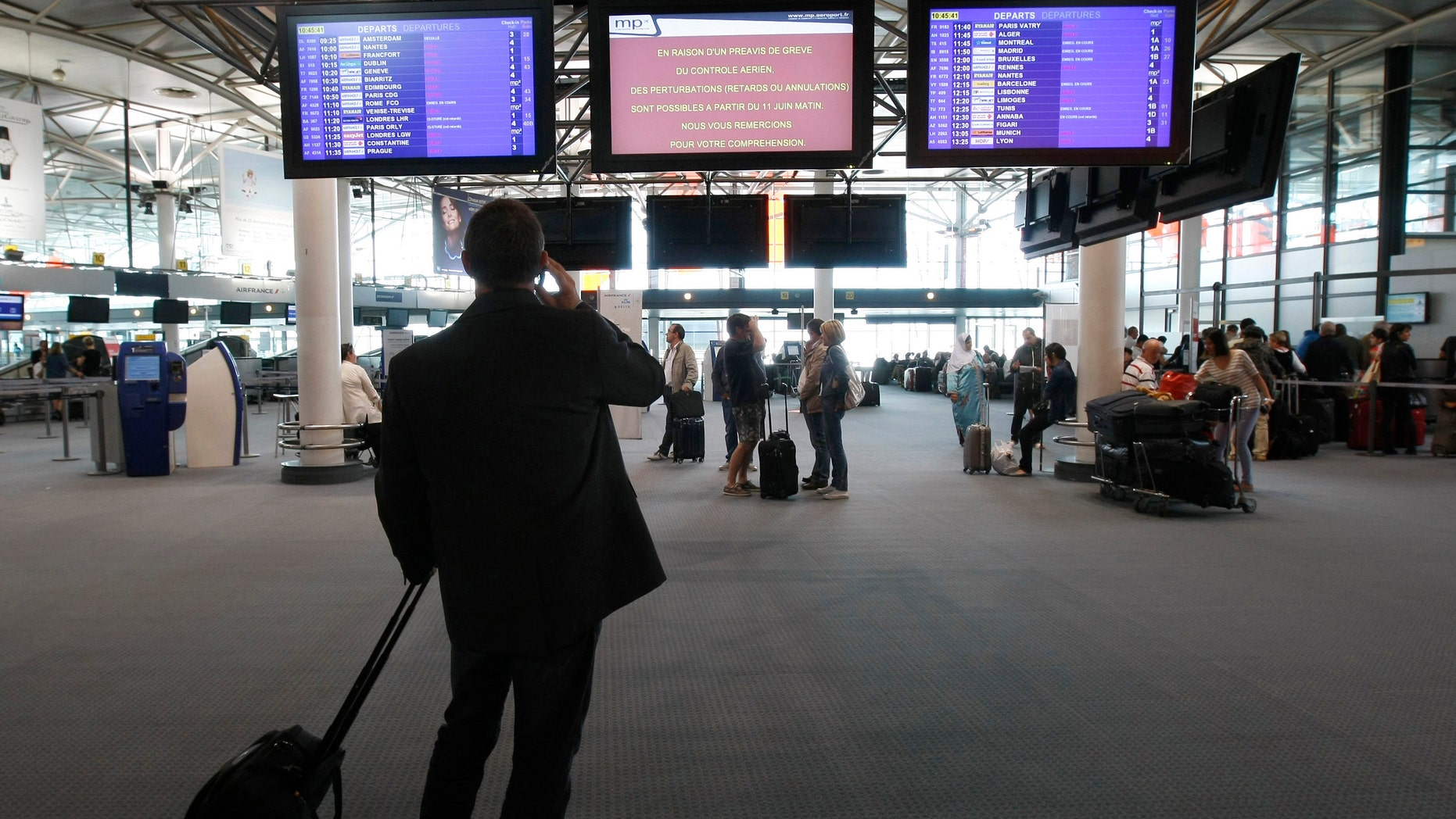 Passengers check flight information at Marseille-Provence Airport, in Marignane, southern France, Tuesday, June 11, 2013.