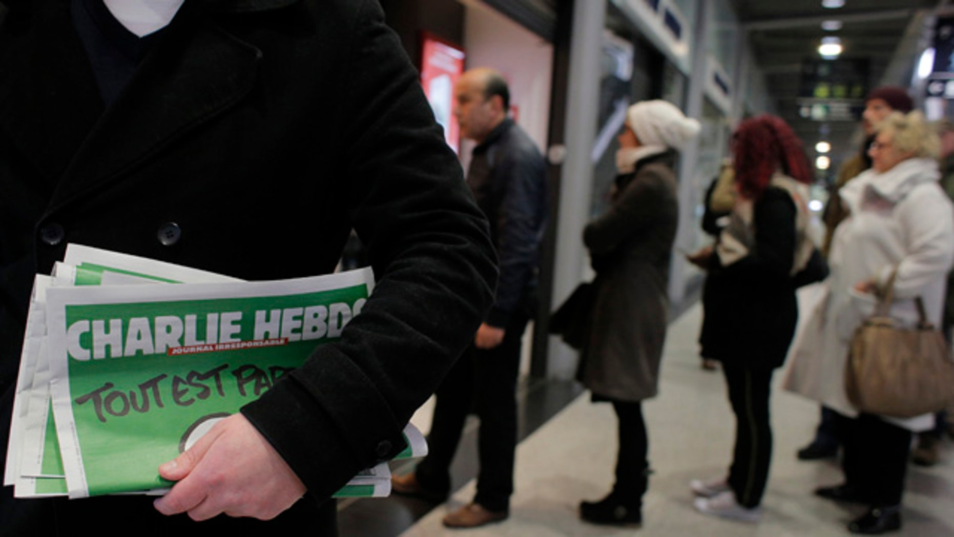 Jan. 14, 2015: A man leaves after buying Charlie Hebdo newspapers as people queue at a newsstand in Paris. (AP Photo/Christophe Ena)