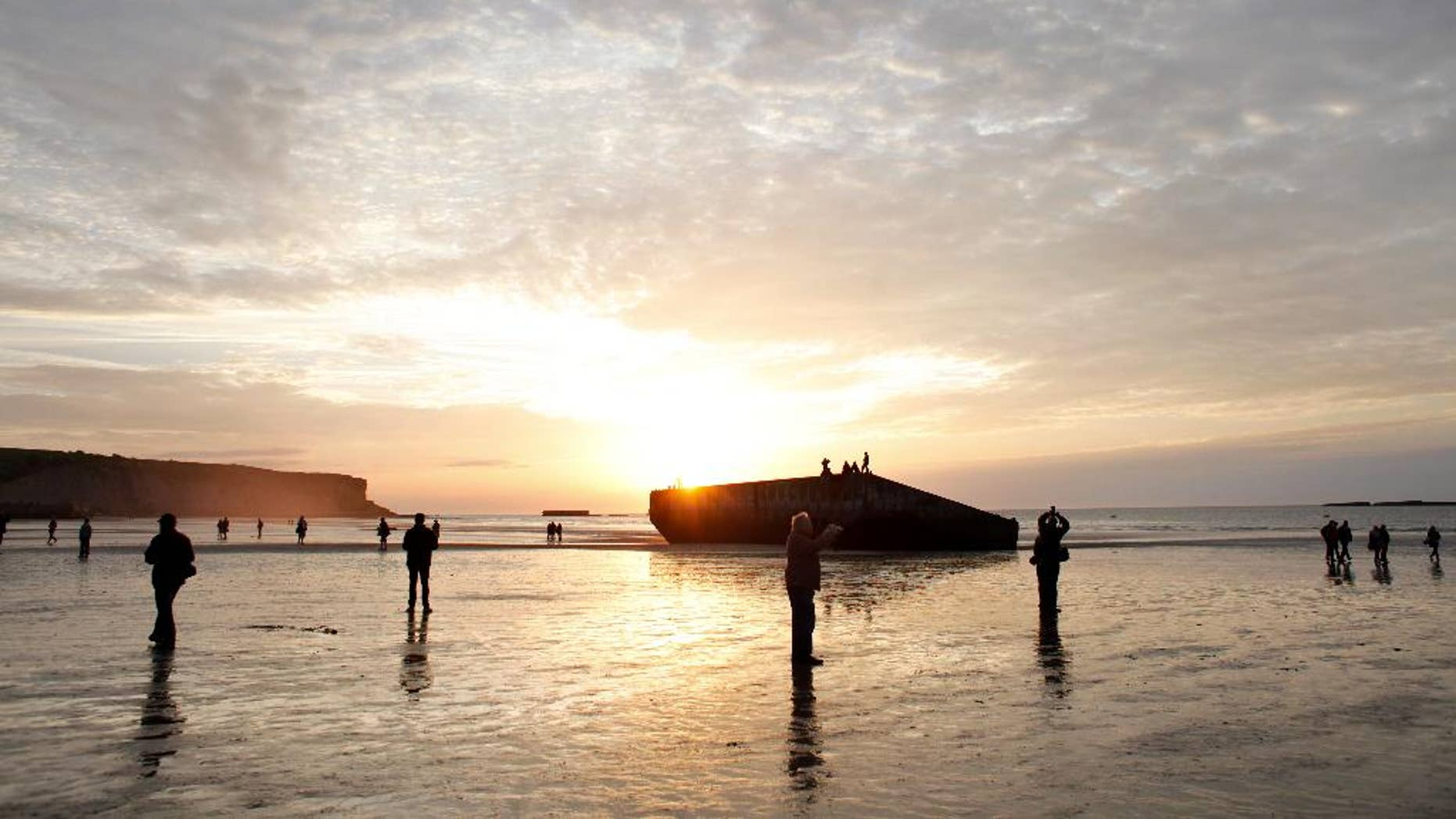 People walk on the beach where remnants of the artificial port of Arromanches, still stand in western France, Thursday June 5, 2014. World leaders and veterans prepare to mark the 70th anniversary of the invasion this week in Normandy. (AP Photo/Thibault Camus)