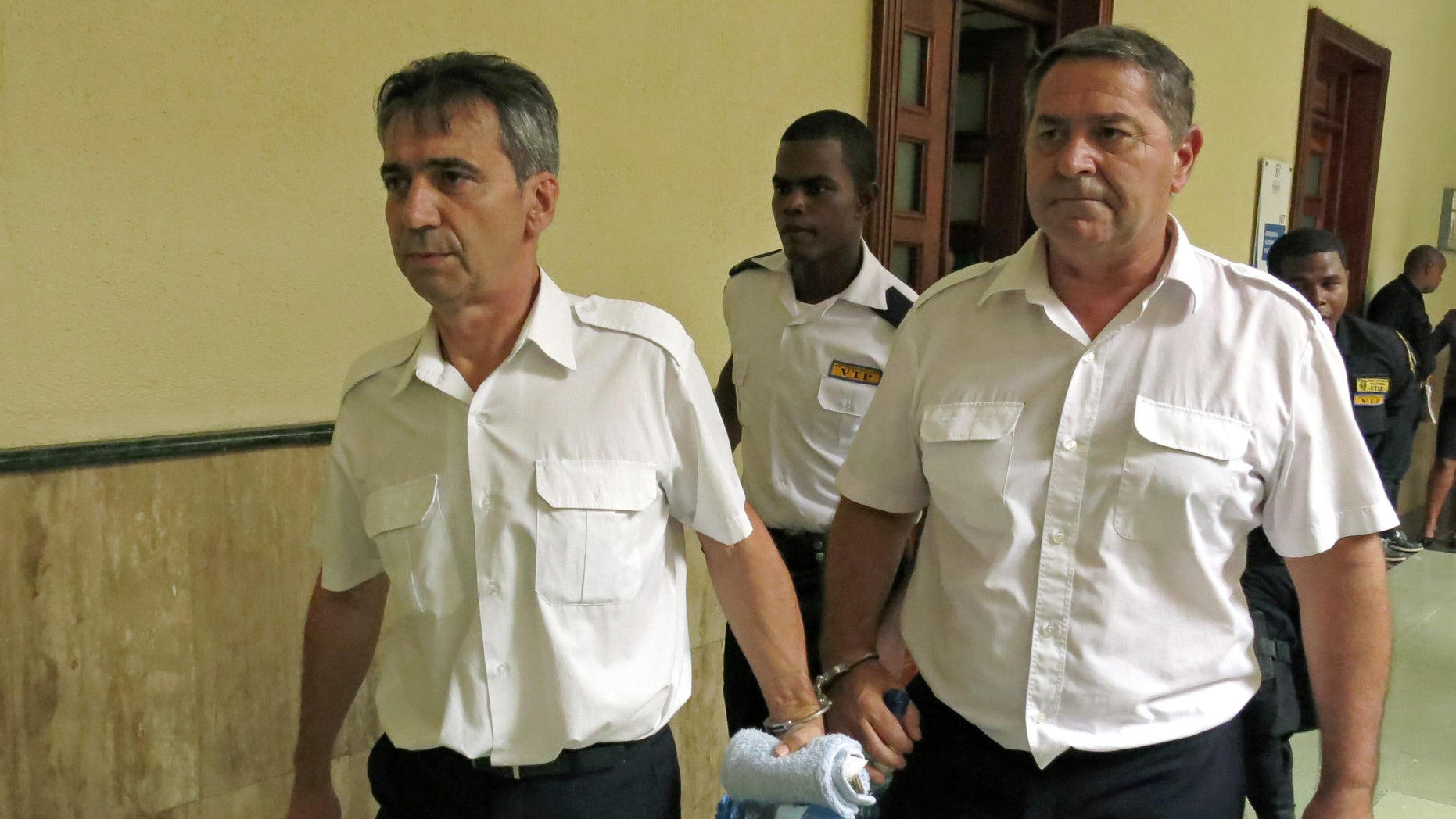 FILE - In this June 17, 2014 file photo, French pilots Bruno Odos, left, and Pascal Jean Fauret, who have been formally charged with drug trafficking, are escorted to a courtroom in Santo Domingo, Dominican Republic (AP Photo/Ezequiel Abiu Lopez, File)
