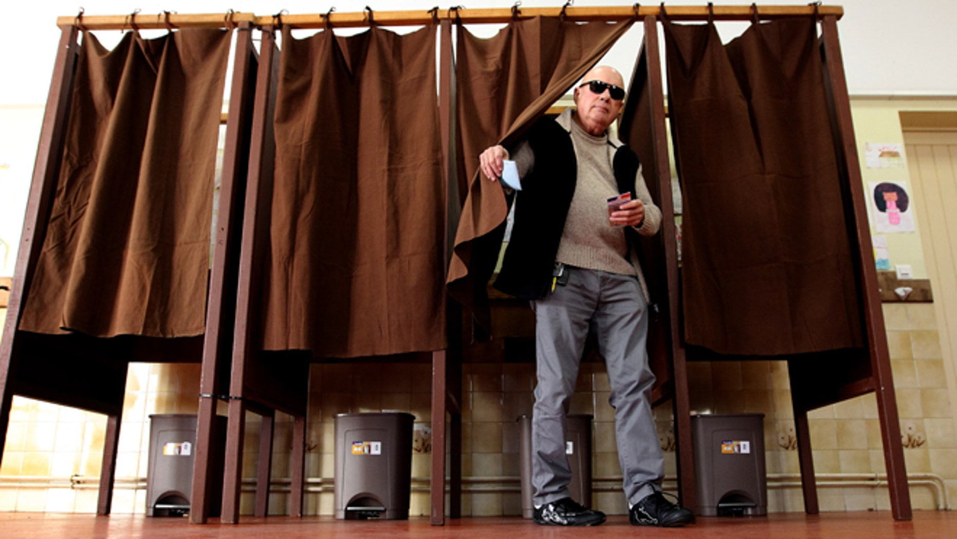 A French man leaves the polling booth before voting in the regional elections.