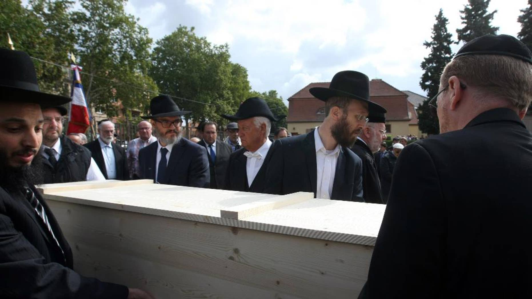 Members of the Jewish community of Strasbourg carry a coffin bearing the remains of a Jewish victim of Nazi anatomist August Hirt, during a ceremony at the Jewish cemetery of Cronenbourg, eastern France, Sunday, Sept. 6, 2015. The remains of Holocaust victims kept for decades in a French medical school were laid to rest on Sunday. (AP Photo/Christian Lutz)