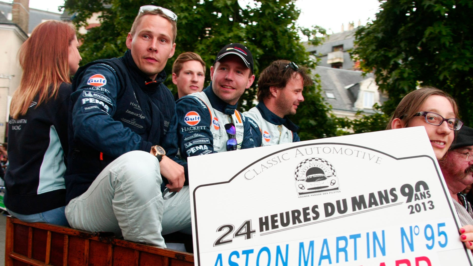 """Danish Driver Allan Simonsen, left, is seen during a parade on the eve of the 90th 24-hour Le Mans endurance race, in Le Mans, western France.. The No.95 Aston Martin Vantage GTE, driven by Simonsen, exited the track at high speed at the """"Tertre Rouge"""" corner on his fourth lap of the race. He died after due to his injuries."""