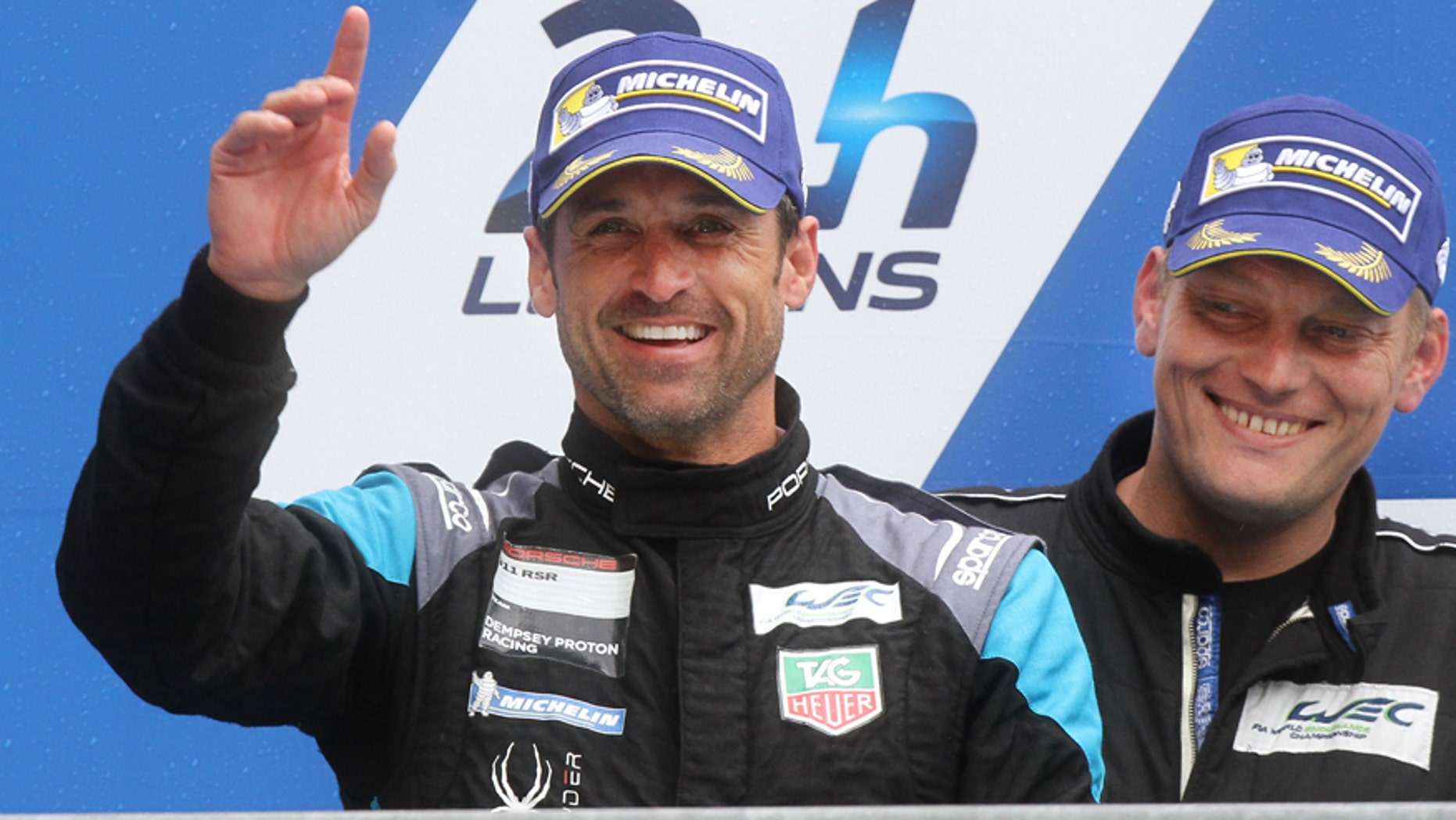 US actor Patrick Dempsey celebrates during the 83rd 24-hour Le Mans endurance race podium ceremony of the LM GTE AM category, as his team finished at the second place, in Le Mans, western France, Sunday, June 14, 2015. (AP Photo/David Vincent)