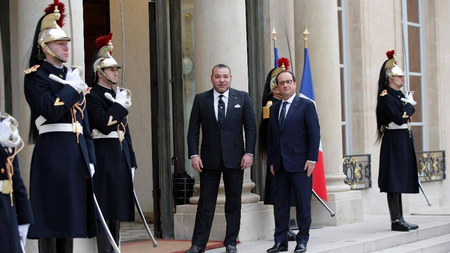 France's President Francois Hollande, right, welcomes Morocco's King Mohammed VI before a meeting at the Elysee Palace, in Paris, France, Monday, Feb. 9, 2015. (AP Photo/Christophe Ena)