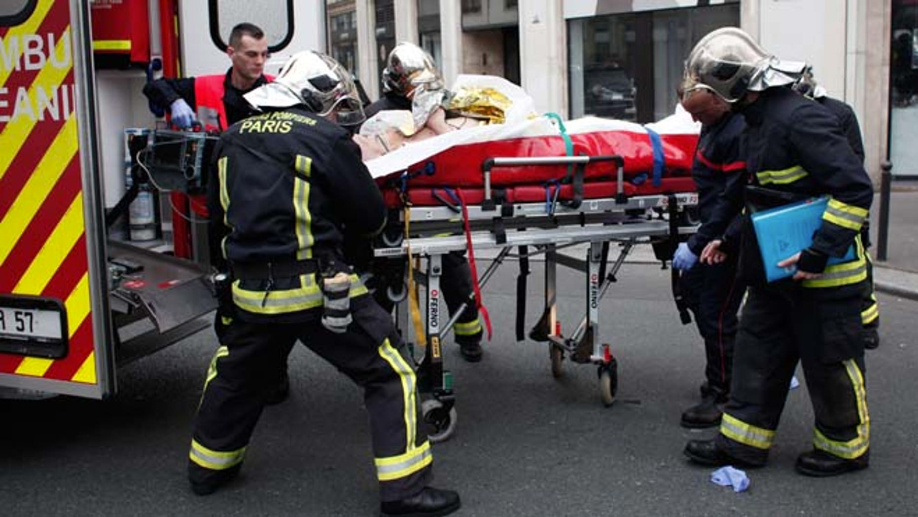 Jan. 7, 2015: An injured person is transported to an ambulance after a shooting, at the French satirical newspaper Charlie Hebdo's office, in Paris. (AP)