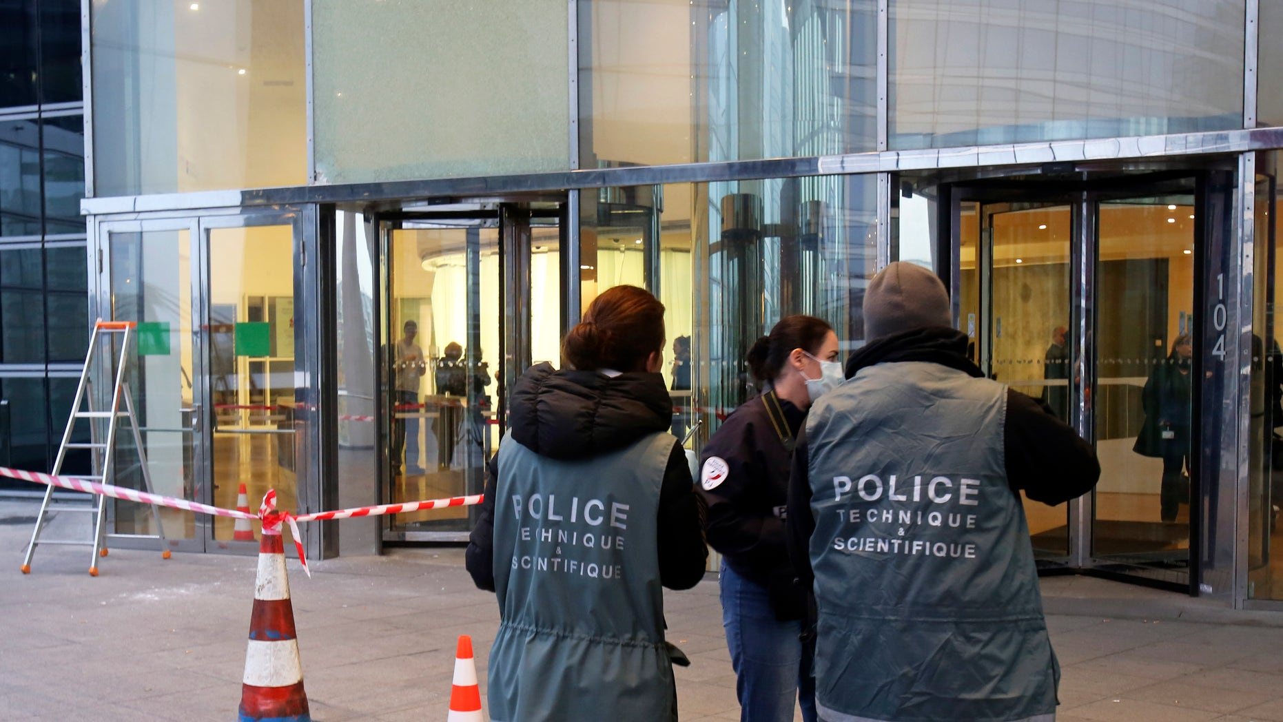 Nov. 18, 2013 - Police officers work at the entrance of the Societe General Bank headquarters in La Defense business district, west of Paris. Soon after a shooting at newspaper Liberation, shots were fired at the headquarters of a major French bank west of Paris, and a gunman briefly took a man hostage nearby. The Paris police headquarters said that it is not clear whether the three incidents are linked, but that authorities are increasing security in all three places as well as media offices around Paris.