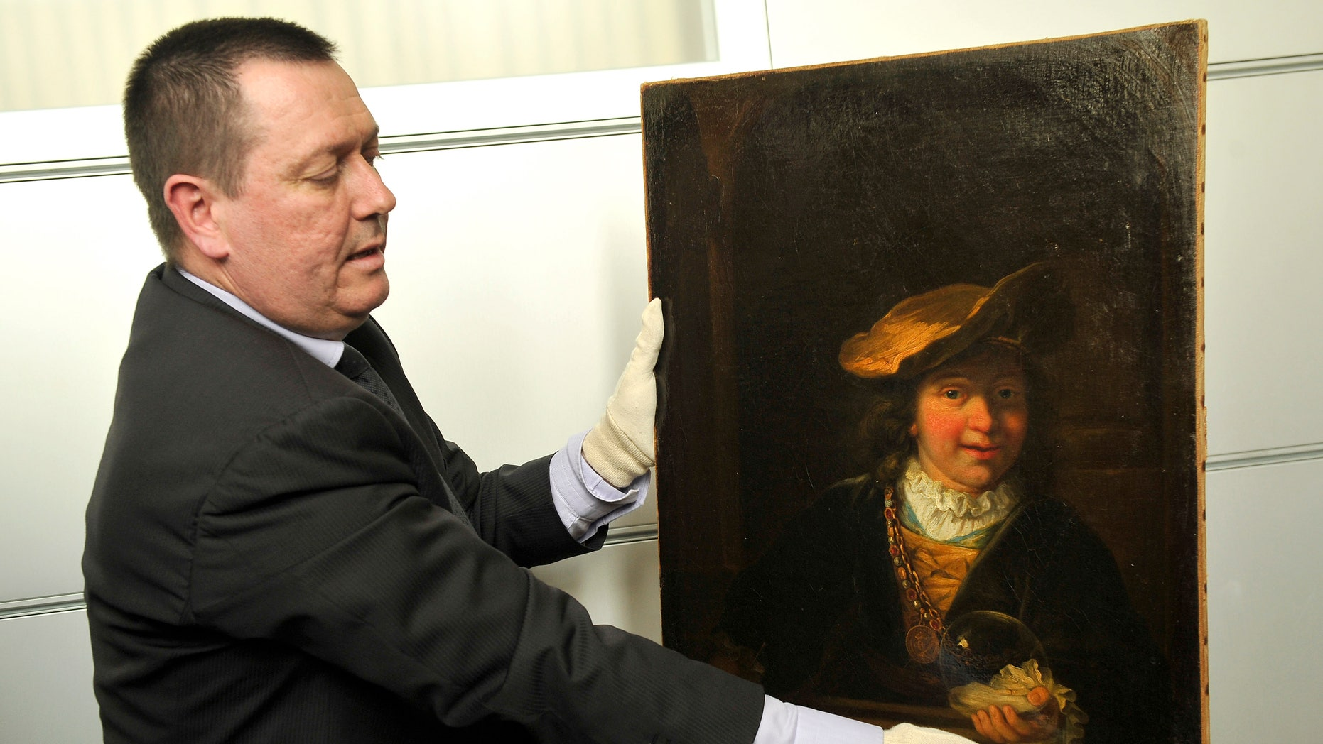 """March 20, 2014 - Policeman Colonel Stephane Gauffeny presents to the press Rembrandt's painting """"Child with a Soap Bubble,"""" stolen in 1999 from the municipal museum of Draguignan, southeastern France. he Rembrandt painting worth millions has been recovered in Nice, and two people found in possession of the Dutch master's painting have been arrested."""
