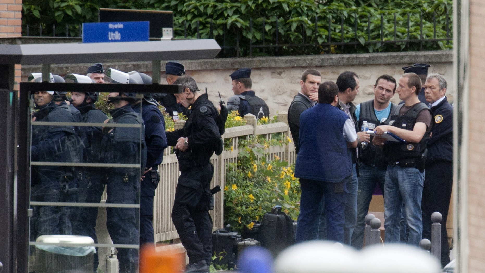 July 10, 2012: Police officers surround a school complex where an armed man took hostages in Vitry sur Seine, south of Paris.