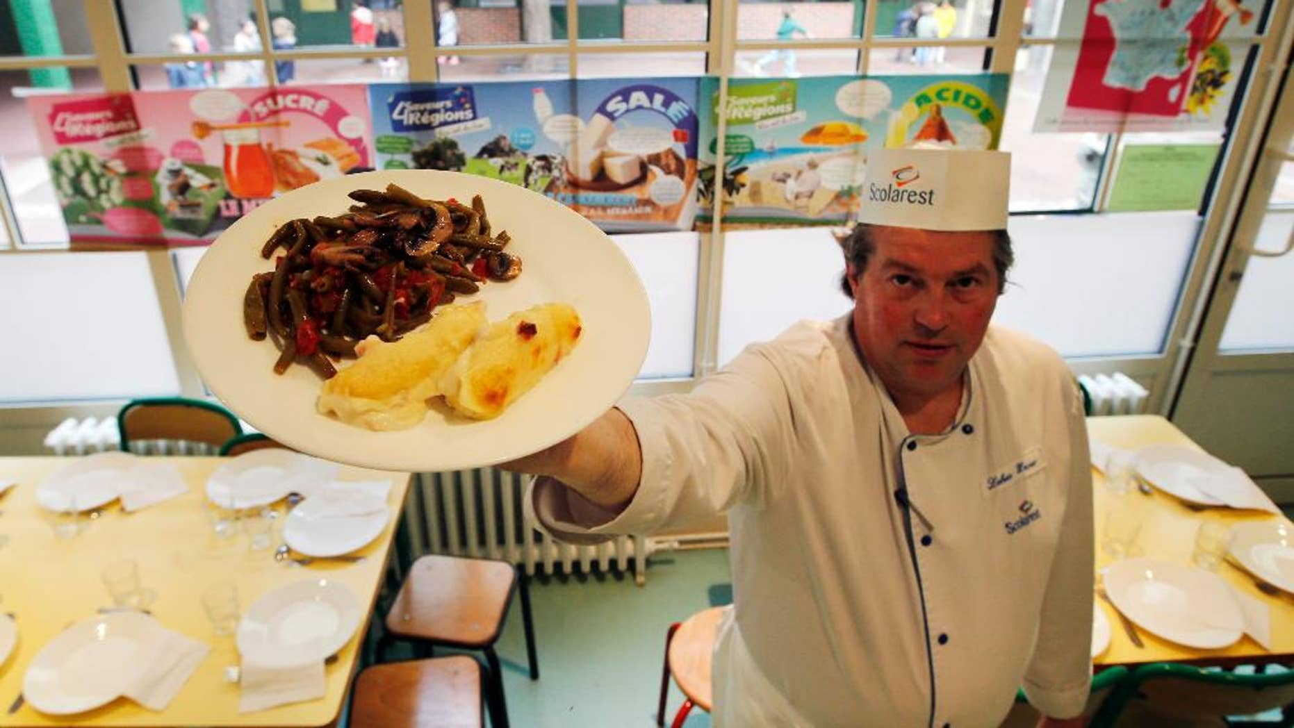 FOR STORY FRANCE SCHOOL LUNCHES - FILE - In this May 6, 2014 file photo, French chef Xavier Lebeau poses with a plate of Quenelles de Brochet (pike fish) with Green Haricot beans and Champignons de Paris (Paris mushrooms), at the Saint Pierre de Chaillot school in Paris, France. France has been grappling with how to reconcile religious beliefs with secular values when it comes to pork in school lunches, with one lawmaker's solution: vegetarian meals. (AP Photo/Francois Mori, File)