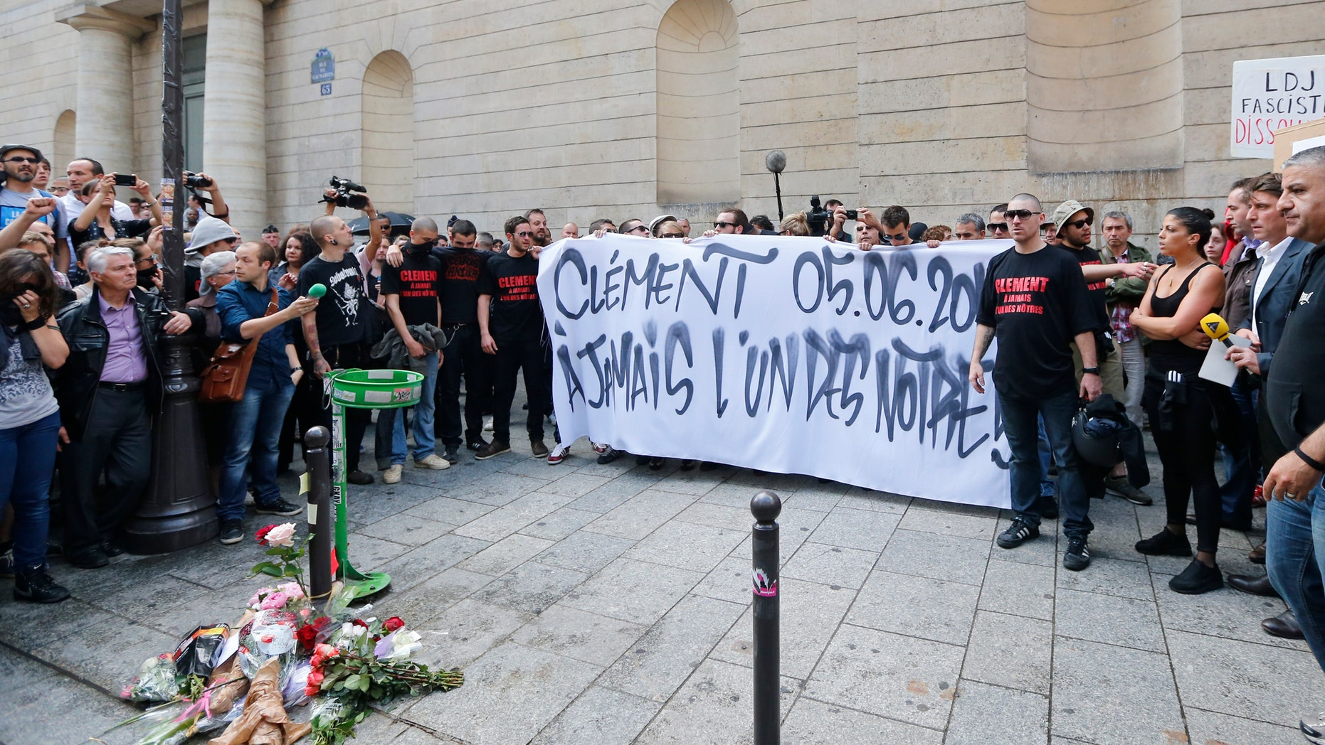 June 6, 2013: French far-left activists gather around flowers which lay  at the foot of a concrete post where Clement Meric, 19, was attacked. A group of skinheads attacked a French far-left activist in the heart of Paris' shopping district, leaving the young man brain-dead in the hospital Thursday, officials said, in an attack that raised fears of increased far-right violence.