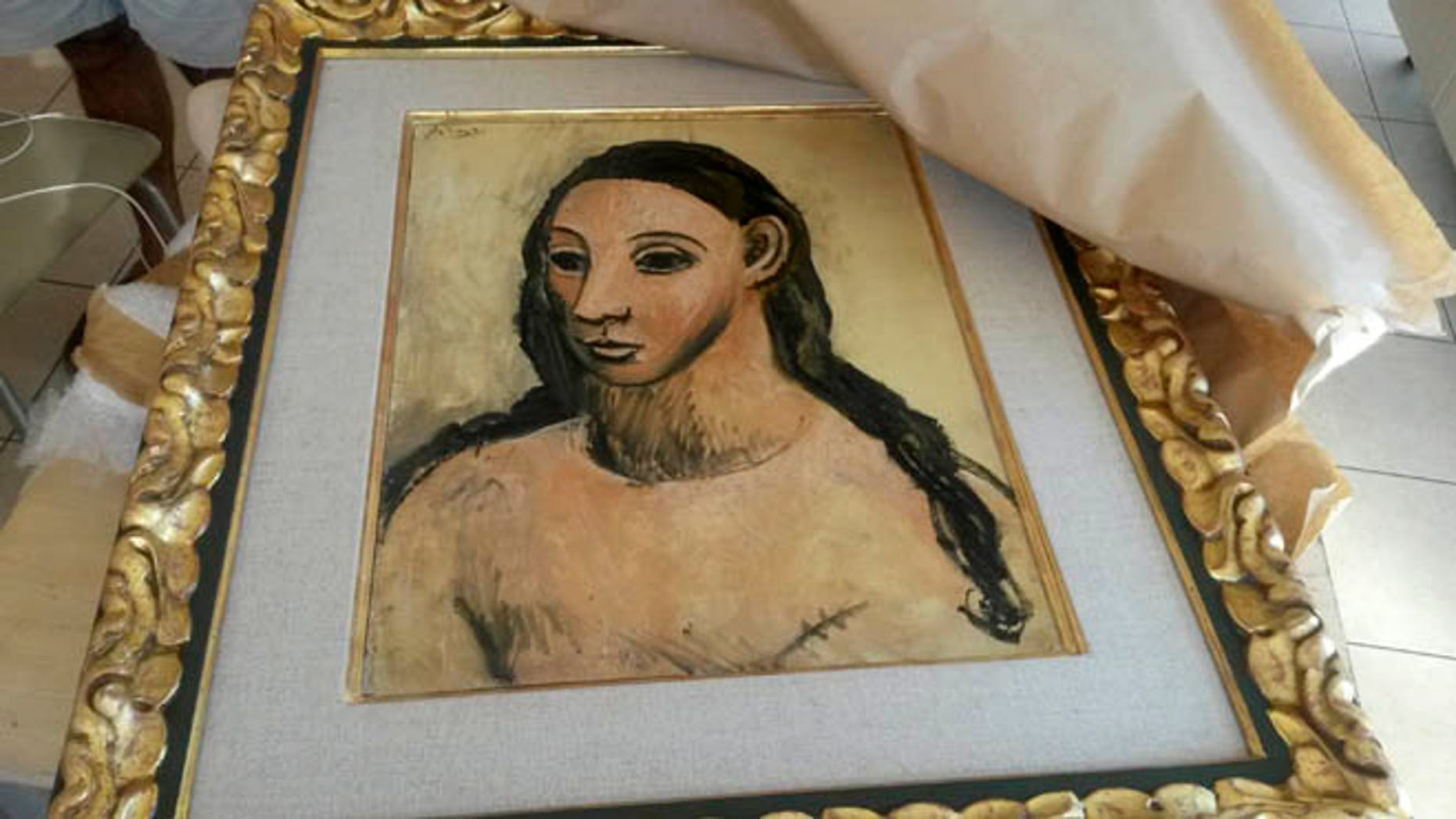 "This photo taken on Friday, July 31, 2015 and made available on Tuesday, Aug. 11, 2015 by French Customs shows a 24 million-euro ($27.4 million) masterpiece by Pablo Picasso, seized from a boat cargo on July 31 from a boat cargo in Corsica, France. Corsican authorities said they were tipped off about an attempted smuggling of the prized 1906 painting, ""Head of a Young Woman,"" to Switzerland. The painting is expected to return to the Reina Sofia museum in Madrid Tuesday, Aug. 11, 2015. (Douane Francaise via AP)"