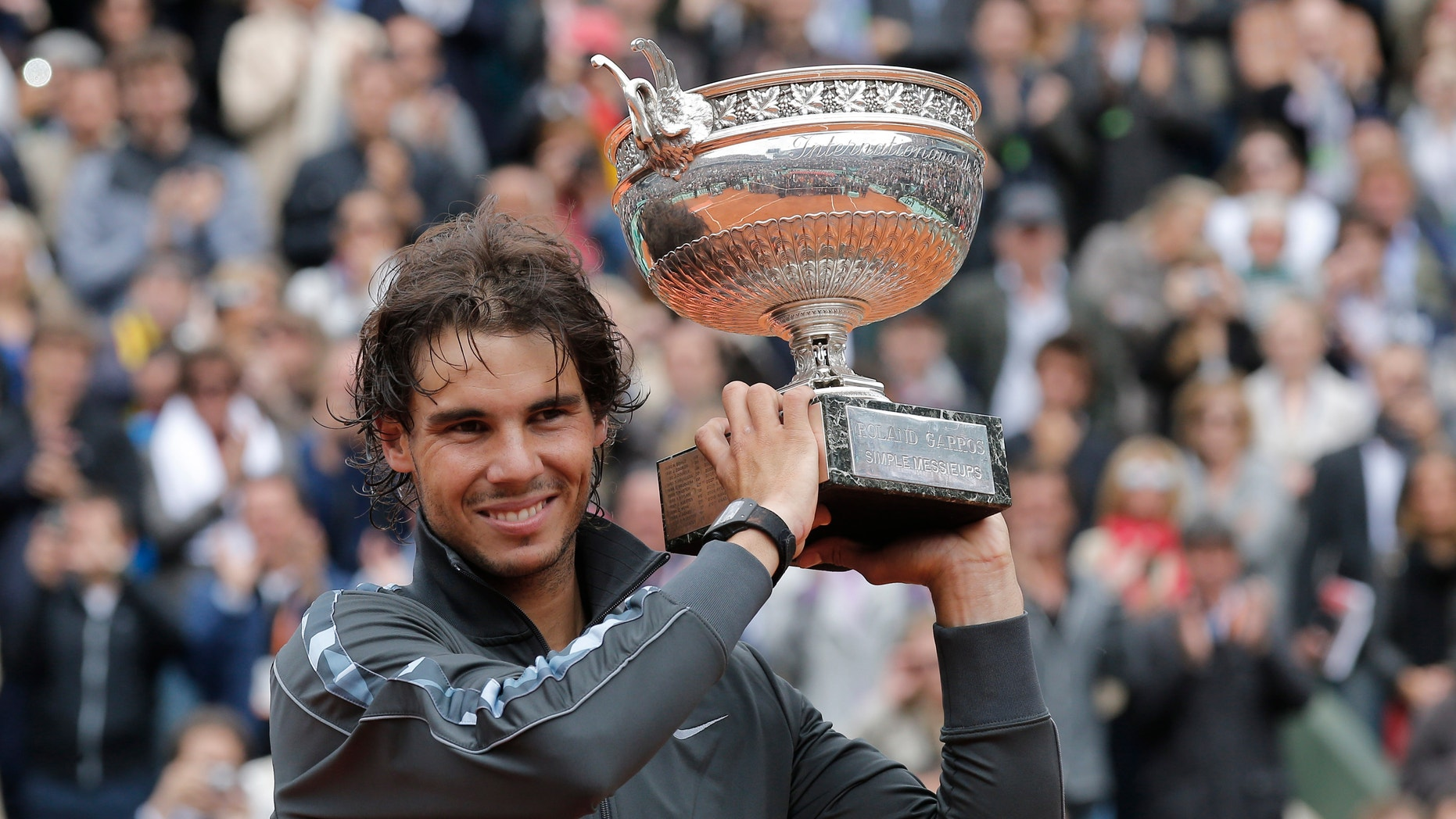 Rafael Nadal, here with his French Open trophy, will carry his country's flag at the Olympics opening ceremony on July 27. (AP Photo)