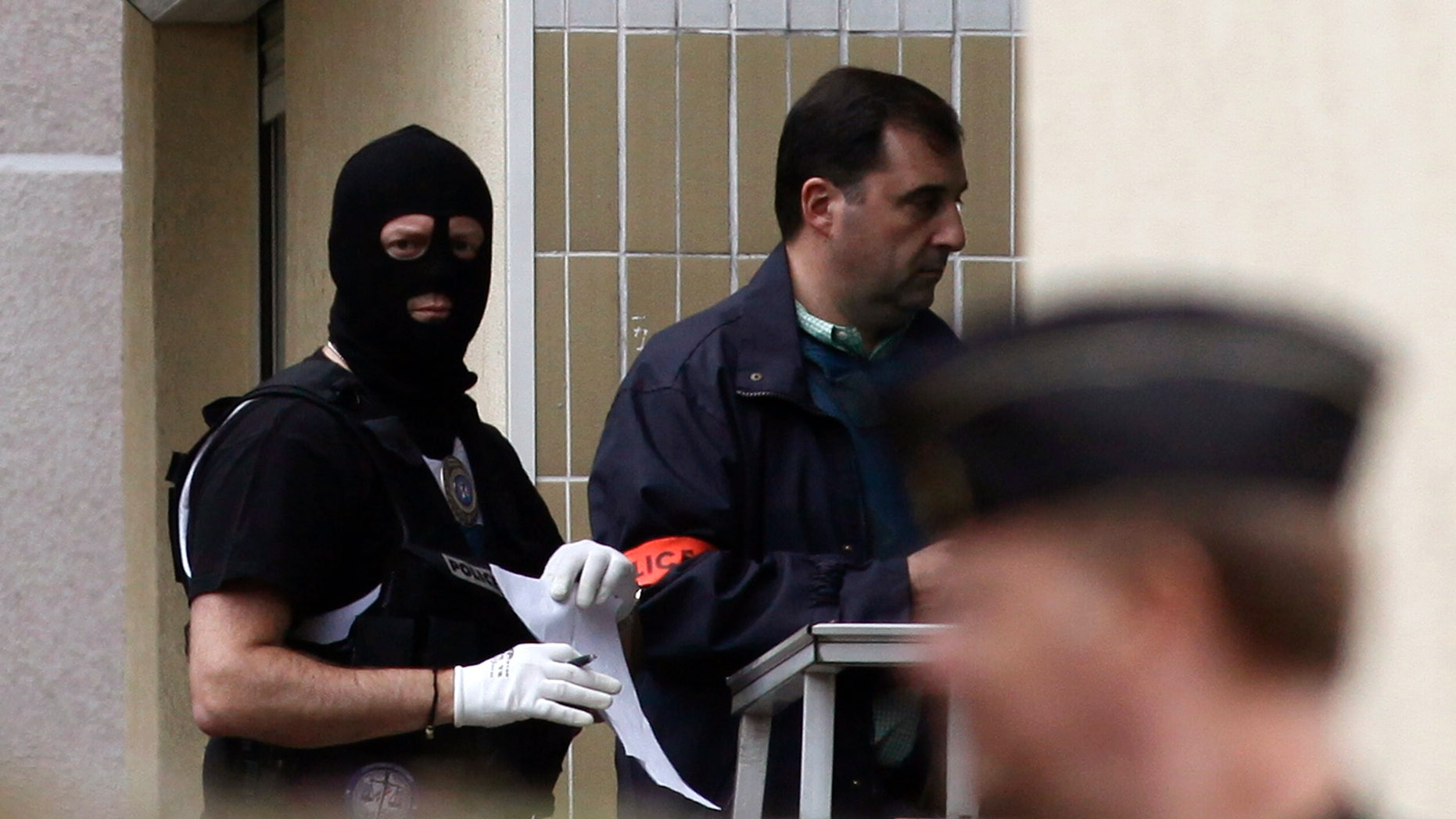 """French police officers stand outside a building where authorities discovered bomb-making material after the break up of a suspected terrorist cell last week, in Torcy, east of Paris, Wednesday, Oct. 10, 2012. French police discovered bomb-making materials in an underground parking lot near Paris as part of a probe of an """"extremely dangerous terrorist cell"""" linked to an attack on a kosher grocery, a state prosecutor said Wednesday. (AP Photo/Thibault Camus)"""