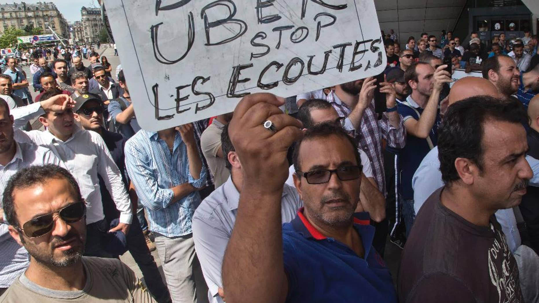 """FILE - This Thursday, June 25, 2015 file photo shows a striking taxi driver holding a placard which read, """"Stop Uber, Stop listening,"""" referring to the new US spying report in France, during a taxi drivers demonstration in Paris, France. French authorities took two Uber managers into custody for questioning on Monday over """"illicit activity"""" involving its low-cost service. The detentions came amid rising tensions between the government and the ride-hailing company, which culminated last week in a violence-marred taxi strike that blocked roads around the country. (AP Photo/Michel Euler, File)"""