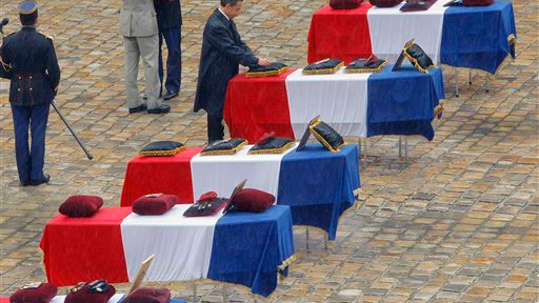 July 19: French President Nicolas Sarkozy pins the Legion of Honor medal on the flag-draped coffins lined up outside the Invalides church, as tribute is paid by France to the seven French soldiers killed last week in Afghanistan.