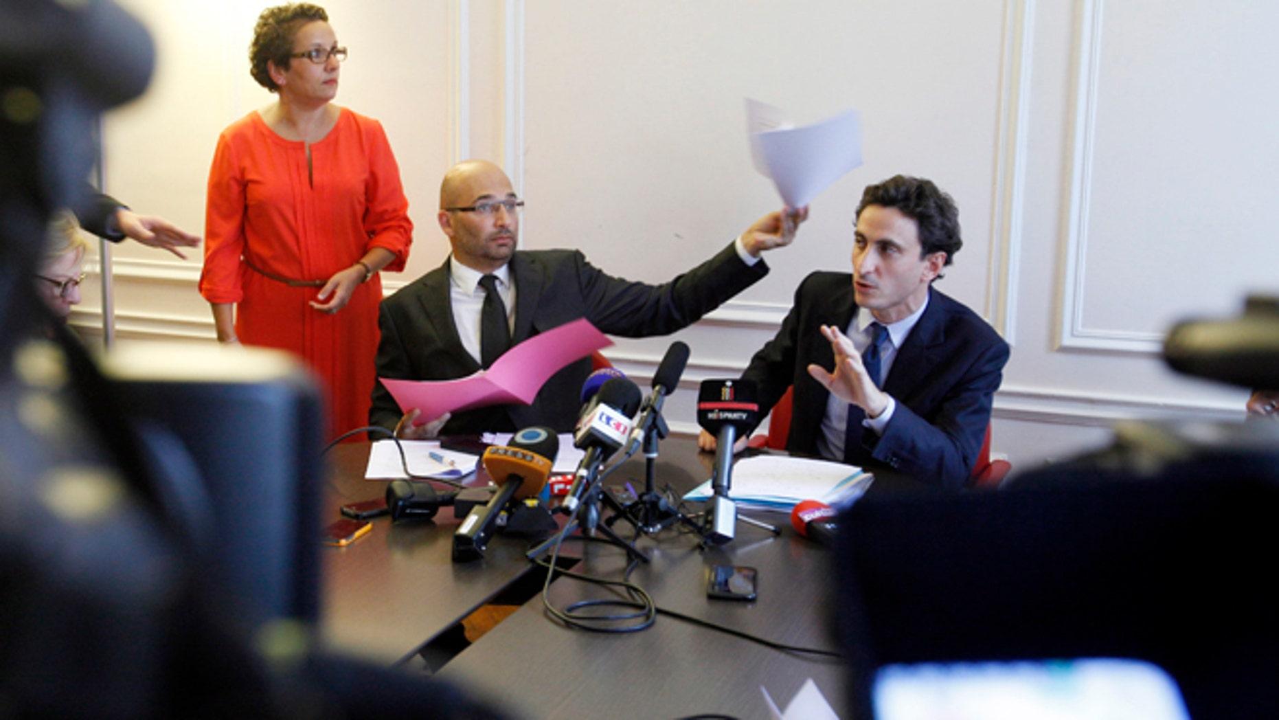 Oct. 2, 2013: Lawyers acting for the plaintiff, Slim ben Achour, left, and Felix de Belloy talk during a press conference in Paris.