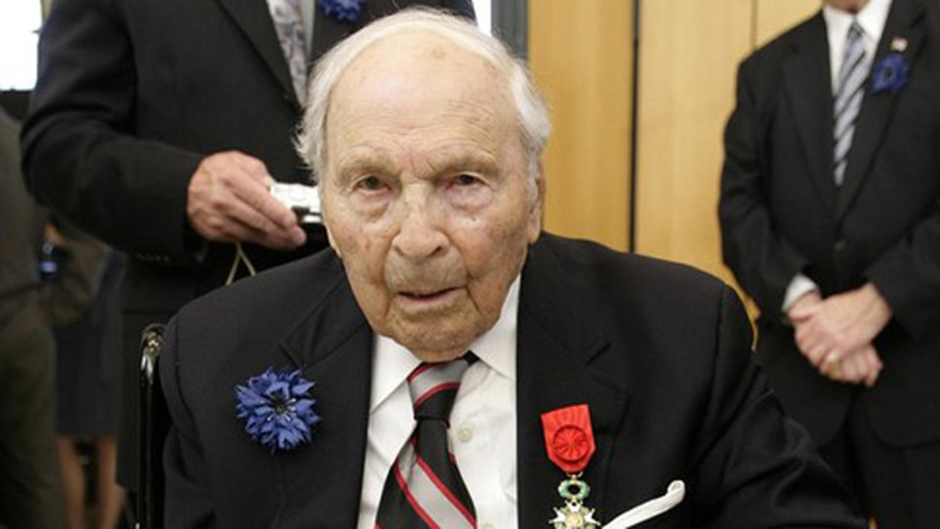 Frank Buckles, then 107, a U.S. veteran of First World War combat in France, signs a World War One era ambulance corps helmet after receiving the Legion of Honor at the French Embassy in Washington in this file image from October 7, 2008.