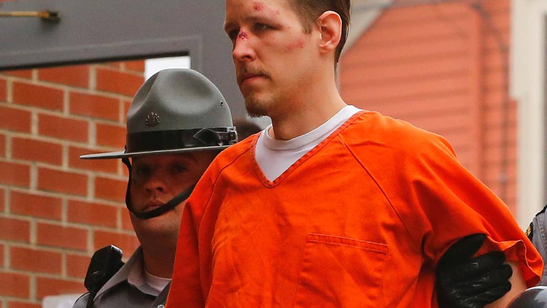 Eric Frein is escorted by police into the Pike County Courthouse for his arraignment in Milford, Pa., Friday Oct. 31, 2014. Frein, was captured seven weeks after police say he killed a Pennsylvania State trooper in an ambush outside a barracks in northeastern Pennsylvania. (AP Photo/Rich Schultz)