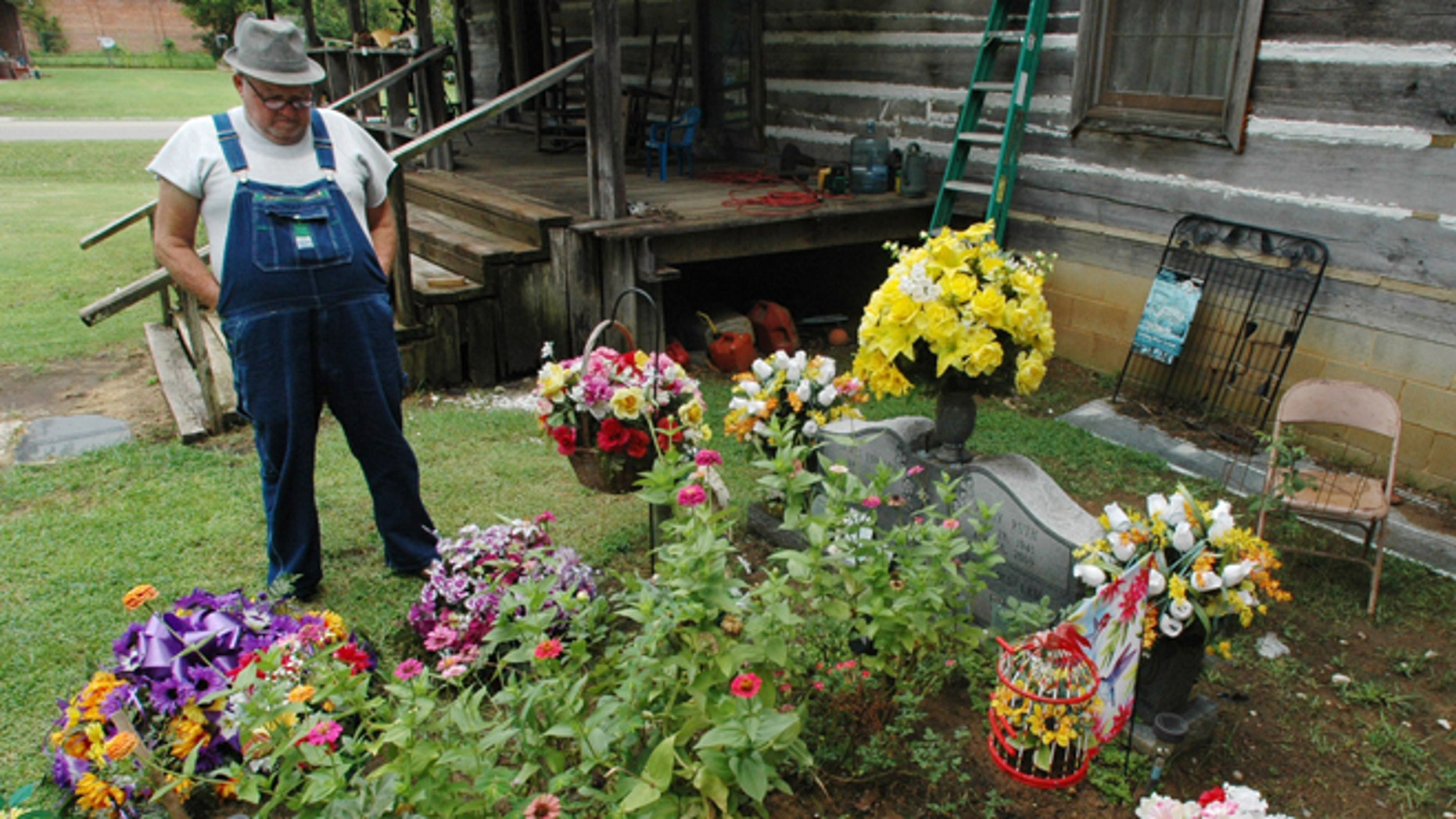 Aug. 10, 2012: In this file photo, James Davis, 73, stands over the grave of his wife, Patsy, in the front yard of the home they shared in Stevenson, Ala.