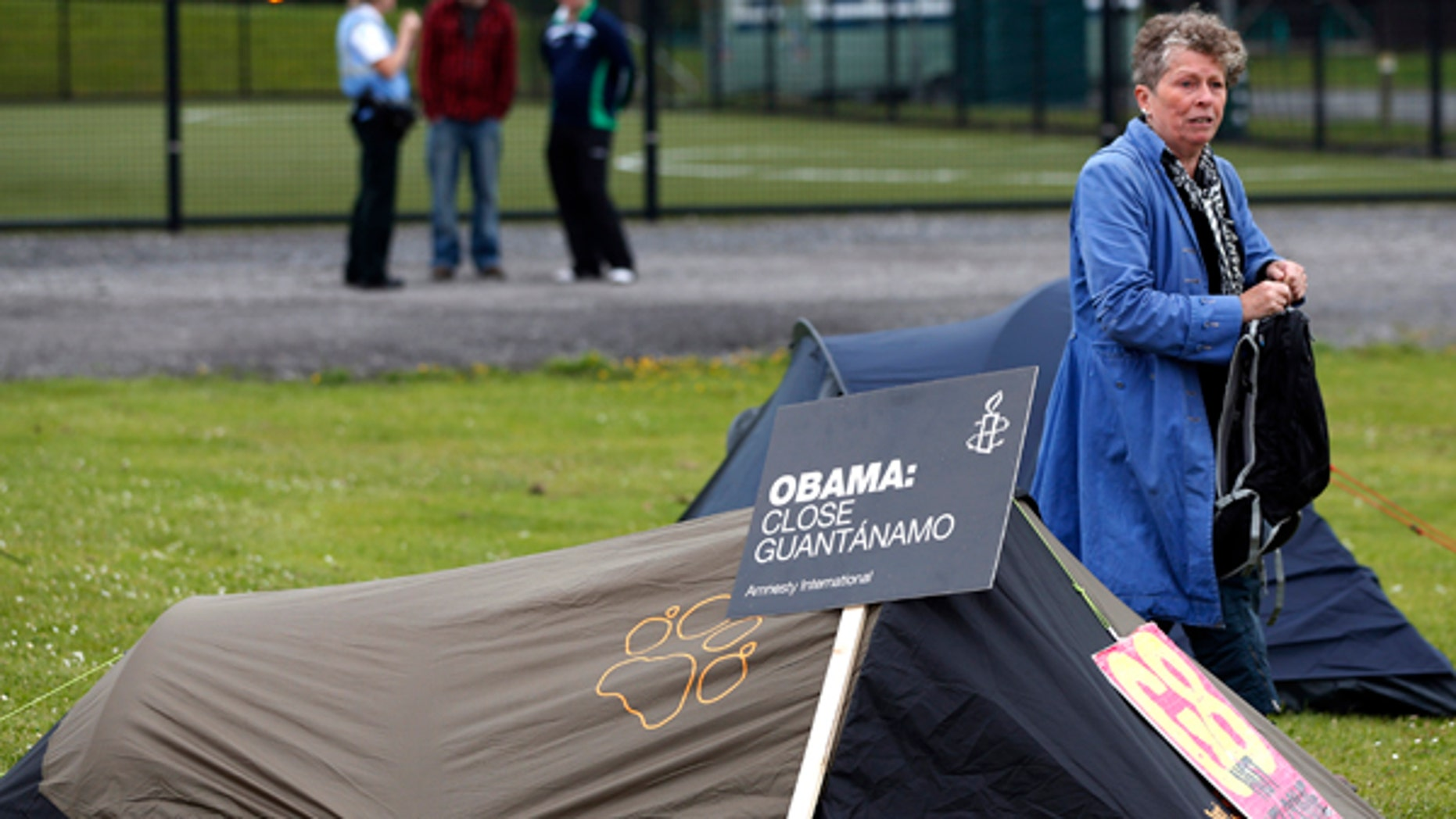 June 16, 2013: A woman walks between signs resting on the tents of demonstrators in a field outside of the G8 summit venue in Enniskillen, Northern Ireland. In a two-day meeting global leaders will discuss the economy and exchange views on foreign affairs and security issues.