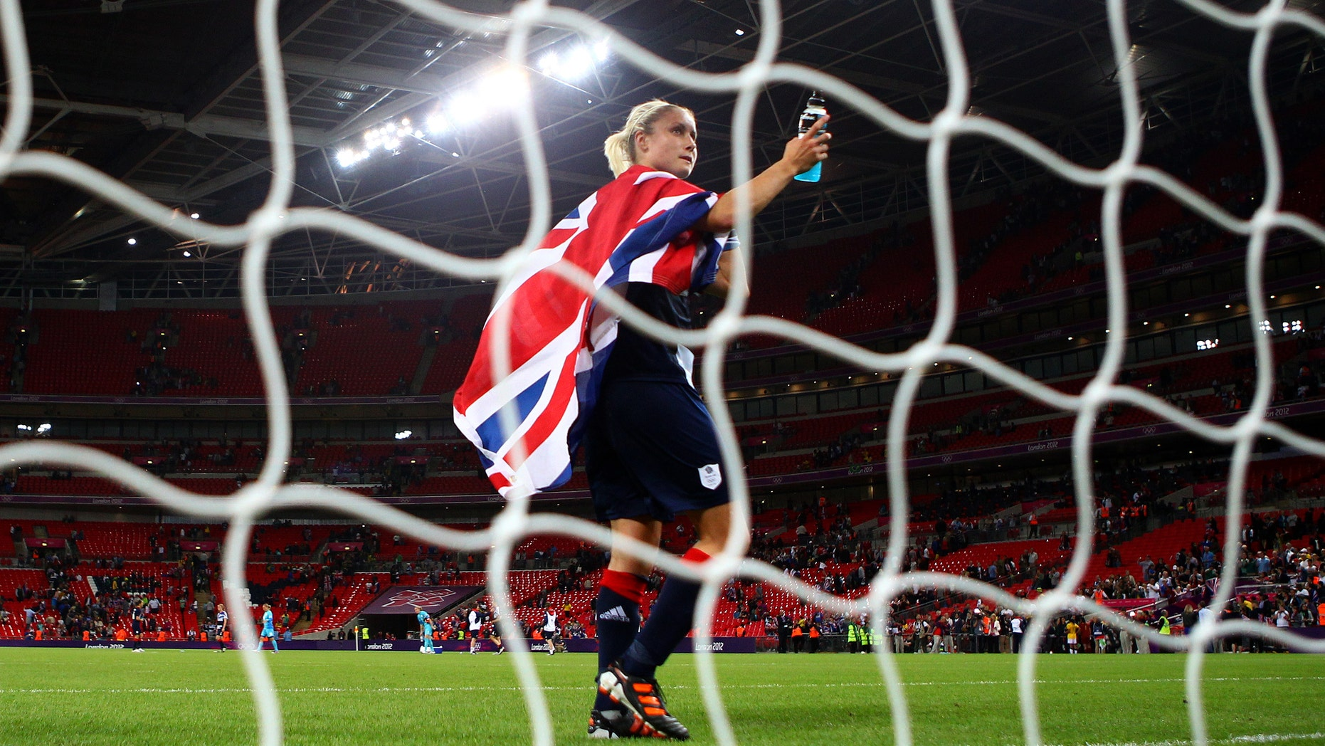 Stephanie Houghton #3 of Great Britain waves to the crowd draped in a Union Jack as she celebrates her team's victory.