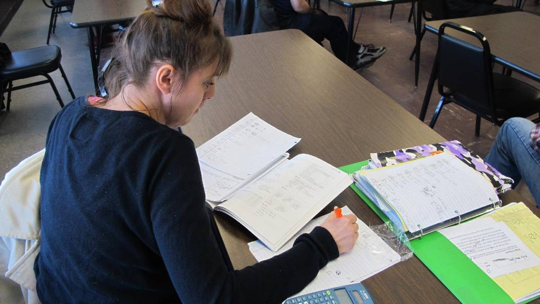 Cheryl Keller, 34, of Cheektowaga practices math problems during an adult education class at the Maryvale Community Education Building in Cheektowaga, N.Y. on March 23, 2015.  Keller is preparing to take the TASC test that New York state now requires for a high school equivalency diploma. The GED was overhauled last year to reflect the Common Core standards that have been adopted by most states and emphasize critical thinking. Two new high school equivalency exams that also incorporate some of those standards were also introduced last year.  (AP Photo/Carolyn Thompson)