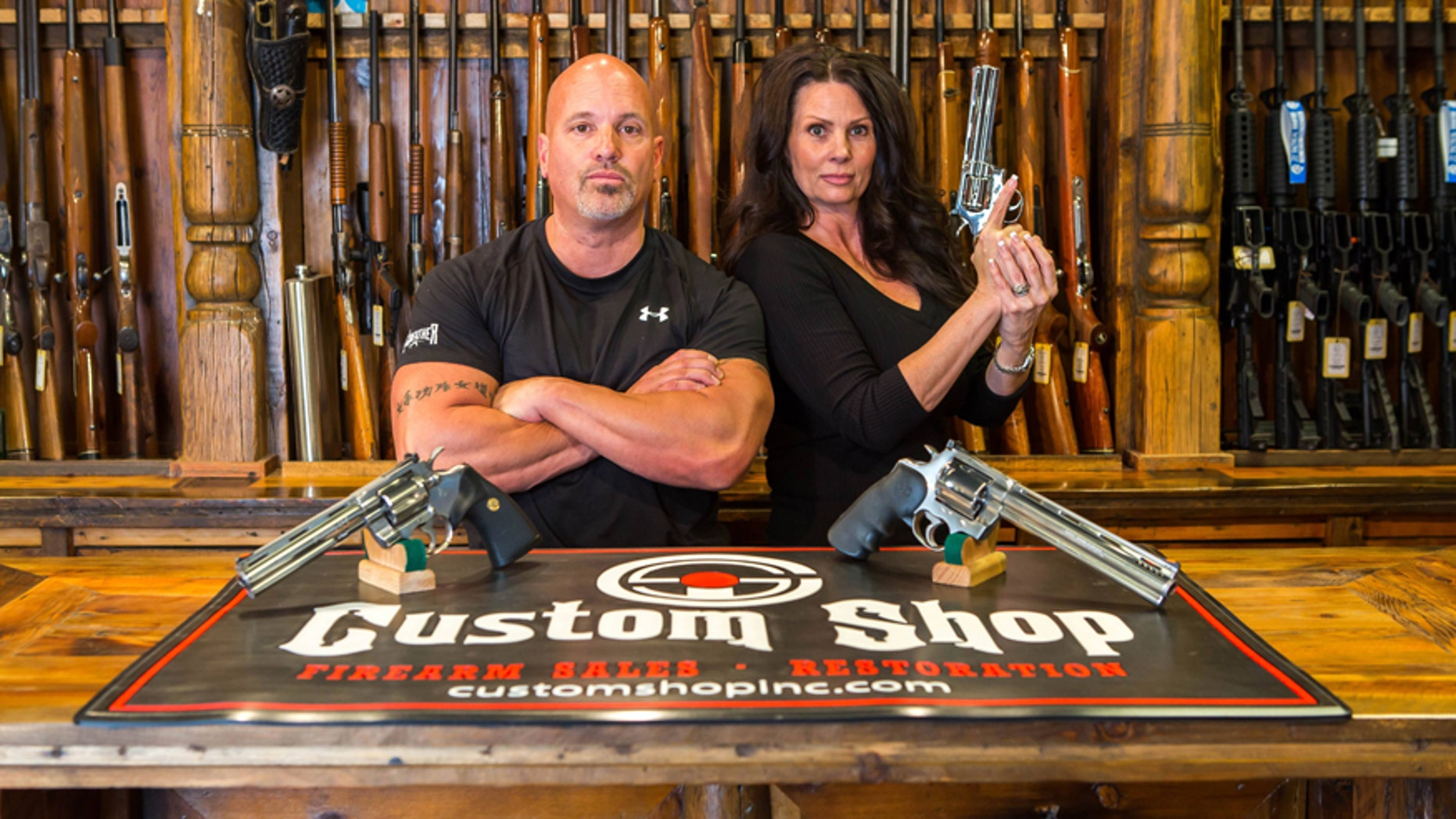 """Lou Tuminaro and his wife Theresa of """"The Gunfather"""" pose in their Hamilton, Montana store The Custom Shop."""