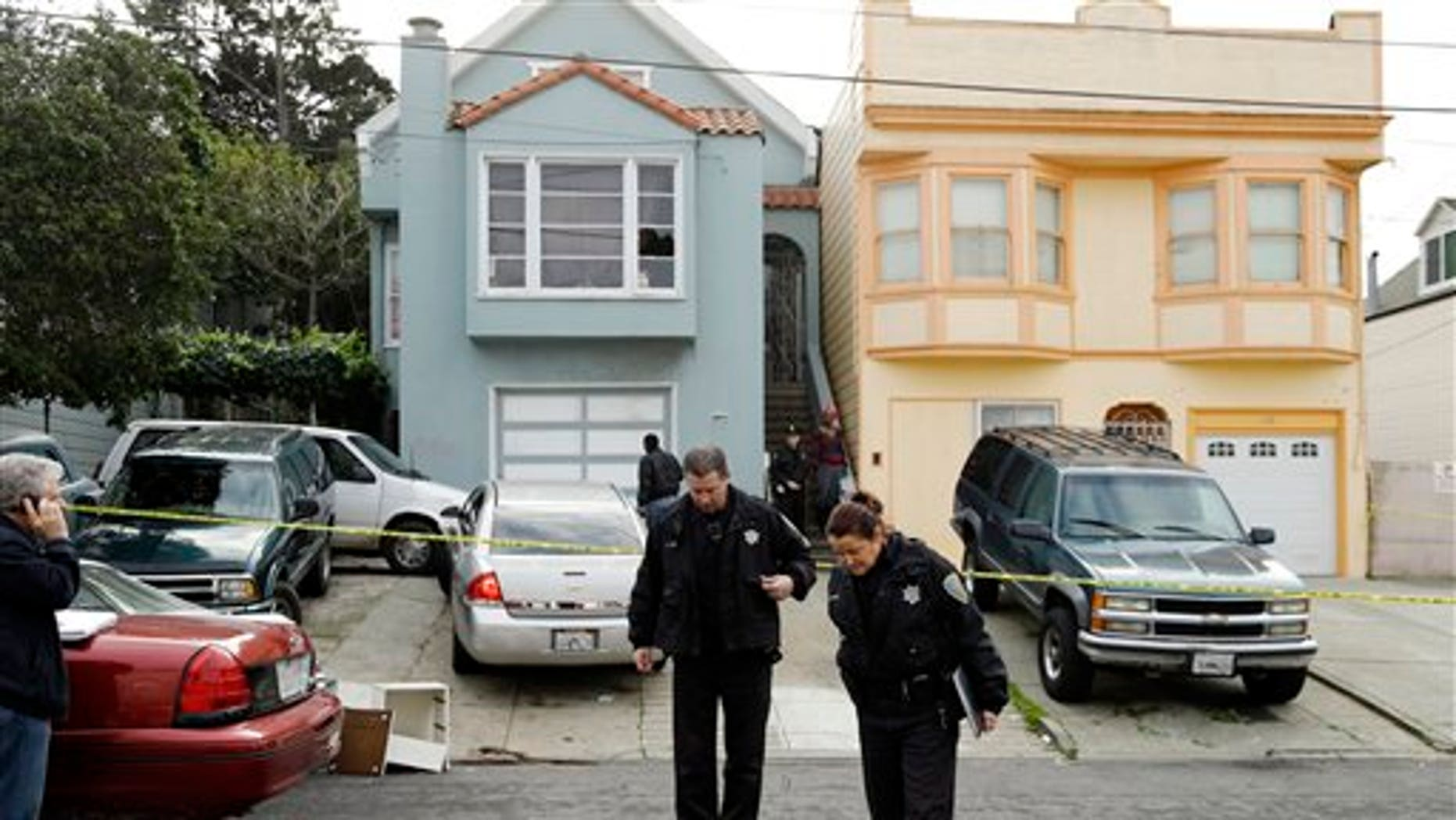 Jan. 6, 2013: San Francisco police officers search for evidence and guard the home of a woman who was set on fire.