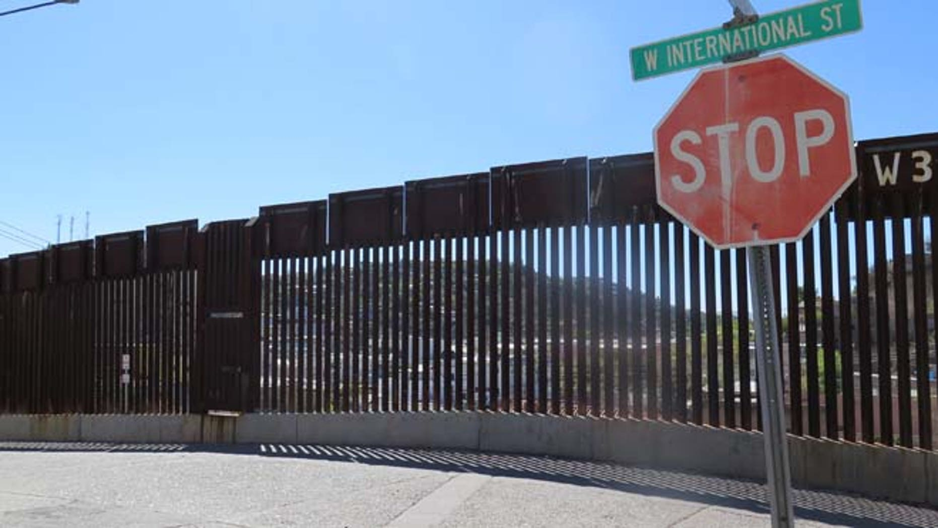 A stop sign in front of the international border fence in Nogales, Ariz.