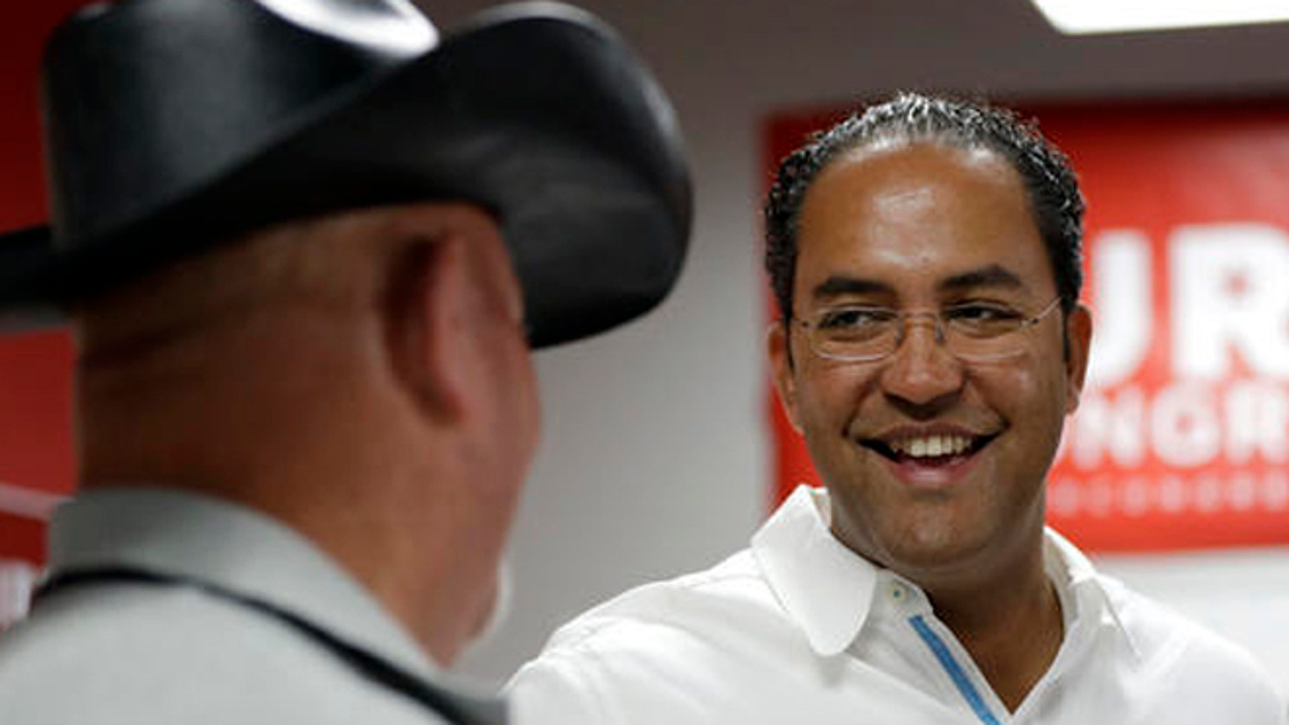 In this Saturday, Aug. 27, 2016 photo, first-term Republican Rep. Will Hurd, right, of Texas, talks with a supporter at a campaign office, in San Antonio. Many House Republican incumbents worry that blowback from Republican presidential nominee Donald Trump's anti-Hispanic rhetoric and promises to build a towering wall the length of the U.S.-Mexico border could hurt their re-election chances, a problem especially acute for those in heavily Latino districts like that of Hurd, whose territory encompasses 820 miles of the U.S.-Mexico border. (AP Photo/Eric Gay)