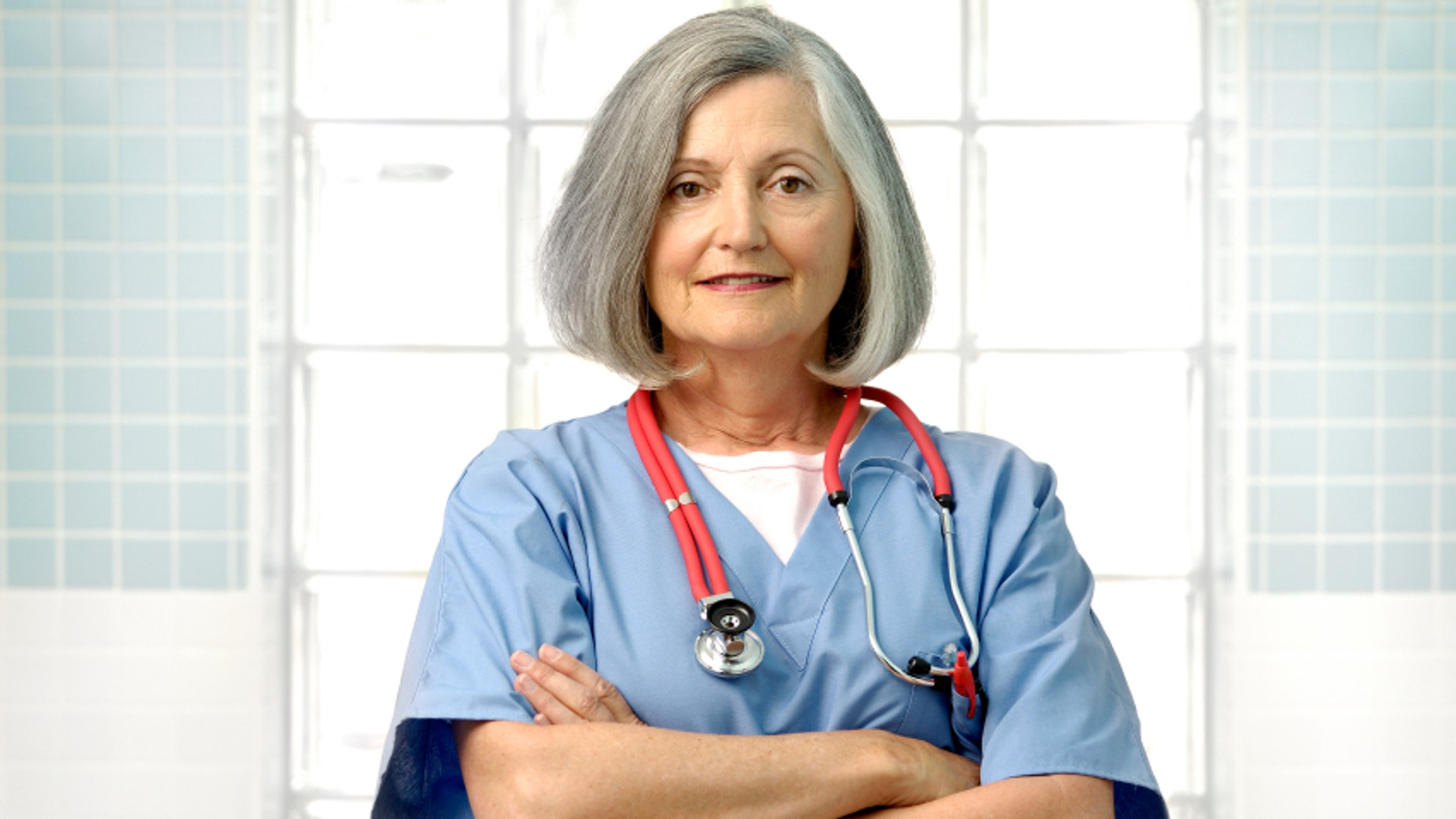 senior female doctor stands with her arms crossed and wears blue scrubs with a  red stethoscope around her neck