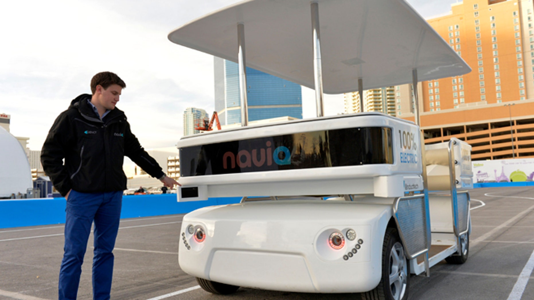 Raphael Gindrat, from Induct, points to a guidance laser while demonstrating their new Navia driverless shuttle at the International Consumer Electronics Show, Monday, Jan. 6, 2014, in Las Vegas. (AP Photo/Jack Dempsey)