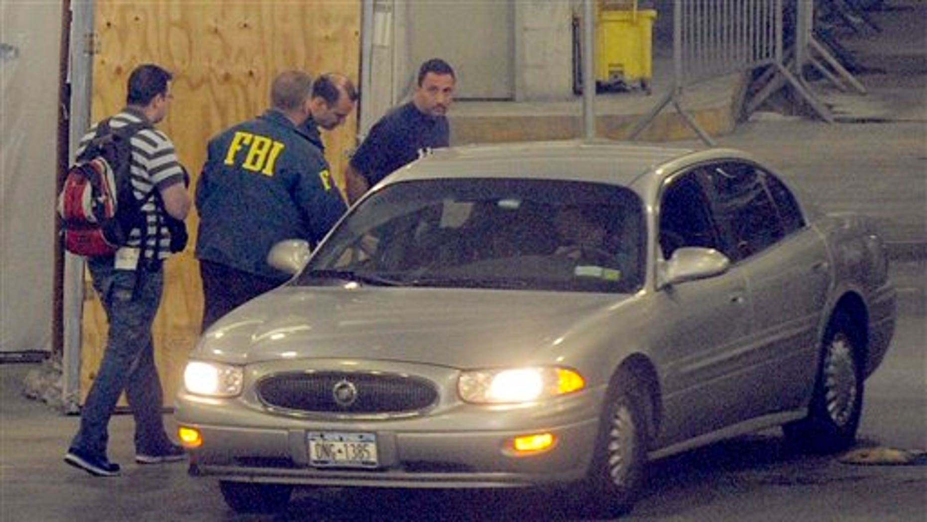 June 2: Richard Palase, standing right, a New York City Police Department detective, was one of 15 people, including two firefighters, who were arrested in connection with a New York City gambling ring, according to federal authorities, in New York. Palase is seen being transferred by FBI agents in the garage of the Jacob K. Javits Federal Building. (AP)