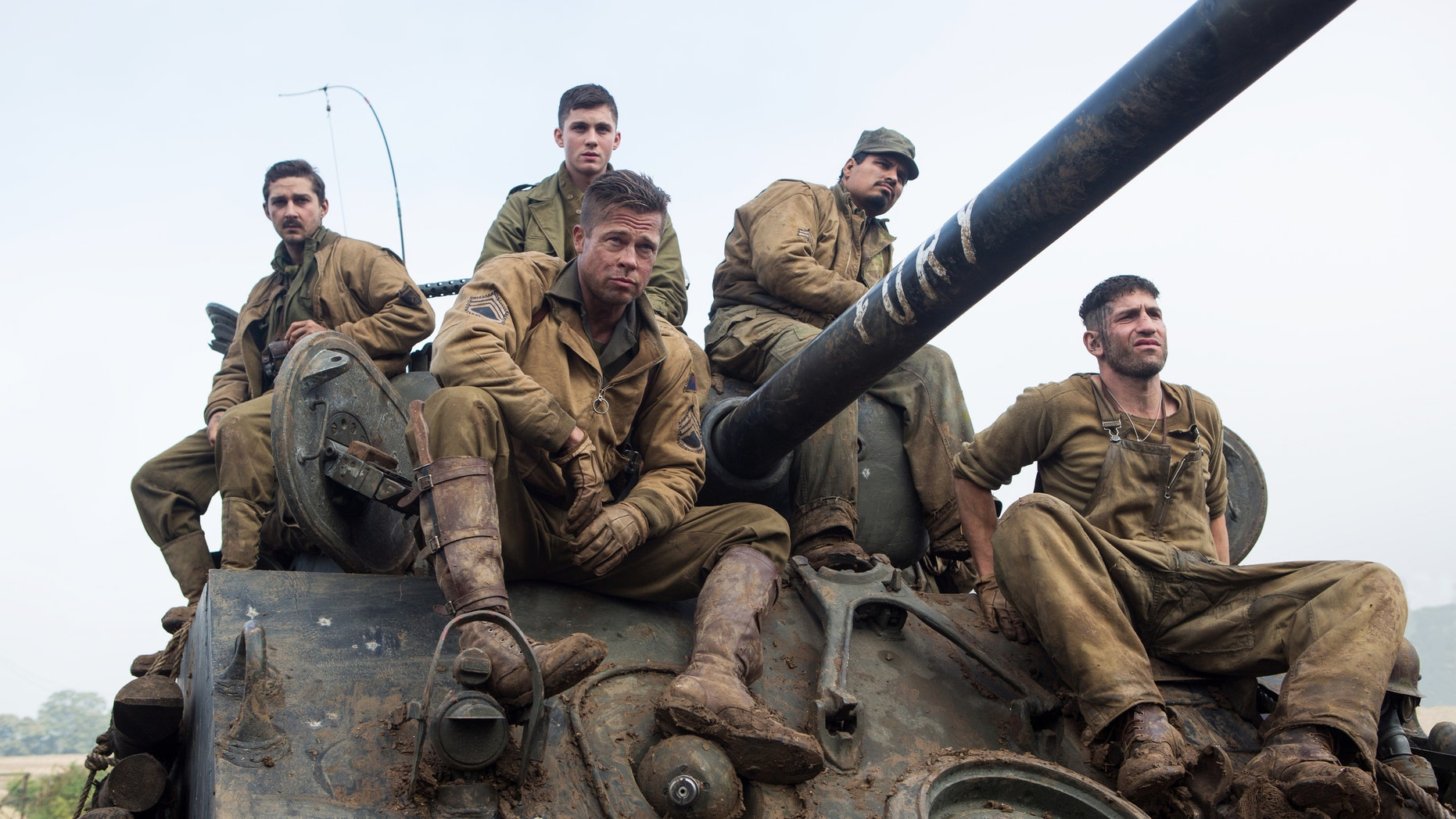 """This photo released by Sony Pictures Entertainment shows, from left, Shia LaBeouf as Boyd """"Bible"""" Swan, Logan Lerman as Norman, Brad Pitt as Sgt. Don âWardaddyâ Collier, Michael Pena as Trini """"Gordo"""" Garcia, and Jon Bernthal as Grady """"Coon-Ass"""" Travis, in Columbia Pictures' """"Fury."""" Before the World War II tank drama reaches theaters Oct. 17, gamers can make like Pitt's character and steer a virtual rendition of the M4A3E8 Sherman tank he commands in the film in the game """"World of Tanks."""" It's the latest example of a likeminded movie and game aligning to hype each other, and it marks the first Hollywood pact for the popular online tank combat title. (AP Photo/Sony Pictures Entertainment, Giles Keyte)"""