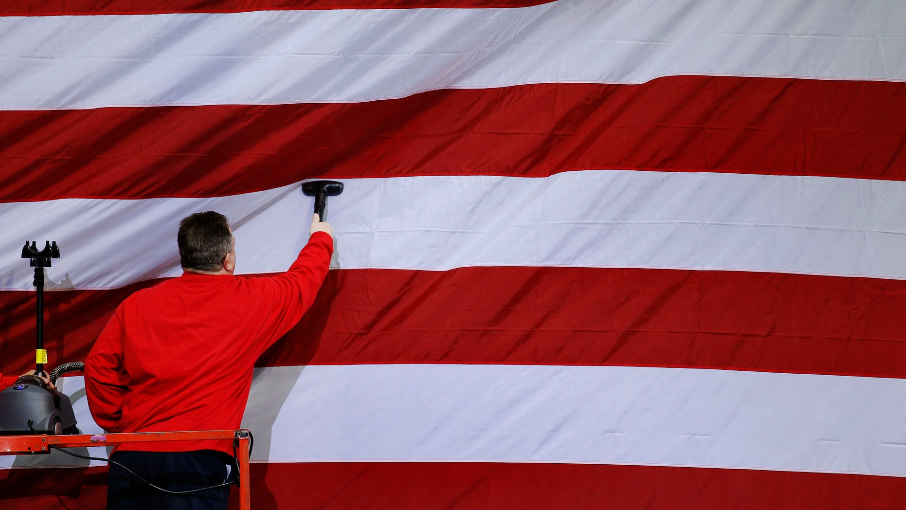 A workman steams a U.S. flag in preparation for a planned visit by President Barack Obama Wednesday, April 6, 2011, at wind turbine manufacture Gamesa Technology Corporation in Fairless Hills, Pa. (AP)