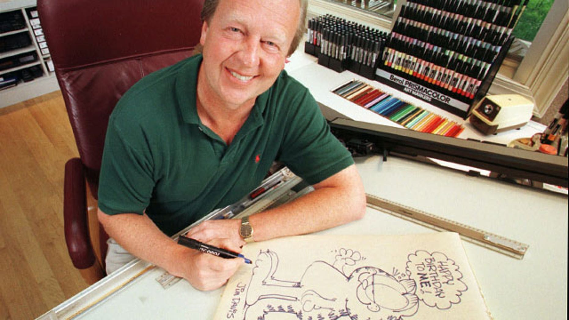 FILE - In this June 9, 1998 file photo, Garfield creator Jim Davis pauses after drawing the cartoon character in his Muncie, Ind., office.