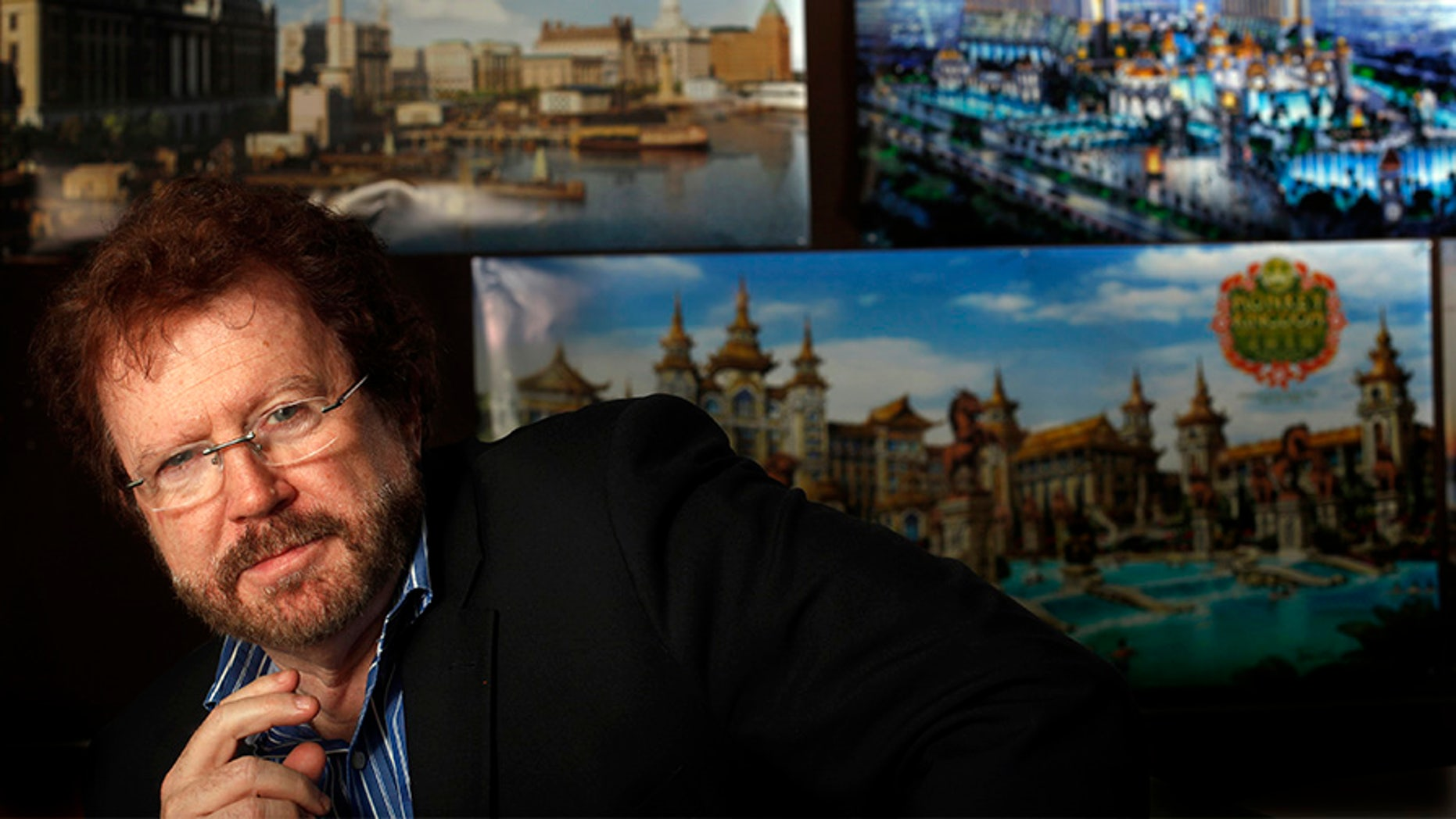 NORTH HOLLYWOOD, CA - JANUARY 15, 2015: Gary Goddard Entertainment founder, Gary Goddard, in his North Hollywood office meeting room with posters of projects he has working in China on JANUARY 15, 2015.  Gary Goddard Entertainment is among many Southern California theme park design businesses that have been getting work in China thanks to a surge in demand for leisure activities in Asia. The posters left to right top row show: the Hengdian Studios recreation of the Shanghai Bund, and the Galaxy Theme Park in Macau and the lower one, the Monkey Kingdom theme park, currently being constructed.  (Photo by Bob Chamberlin/Los Angeles Times via Getty Images)