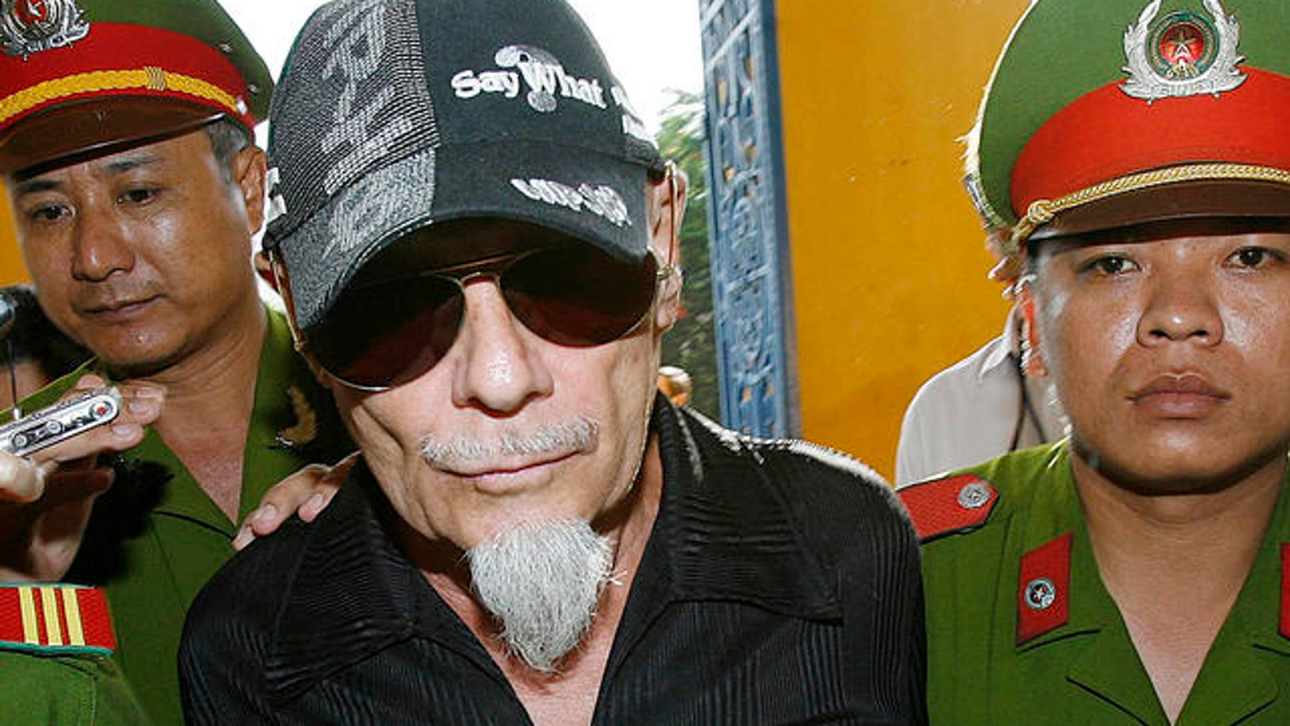 2006: Gary Glitter, former British rock singer, is led into court, Ho Chi Minh city, Vietnam. (AP)