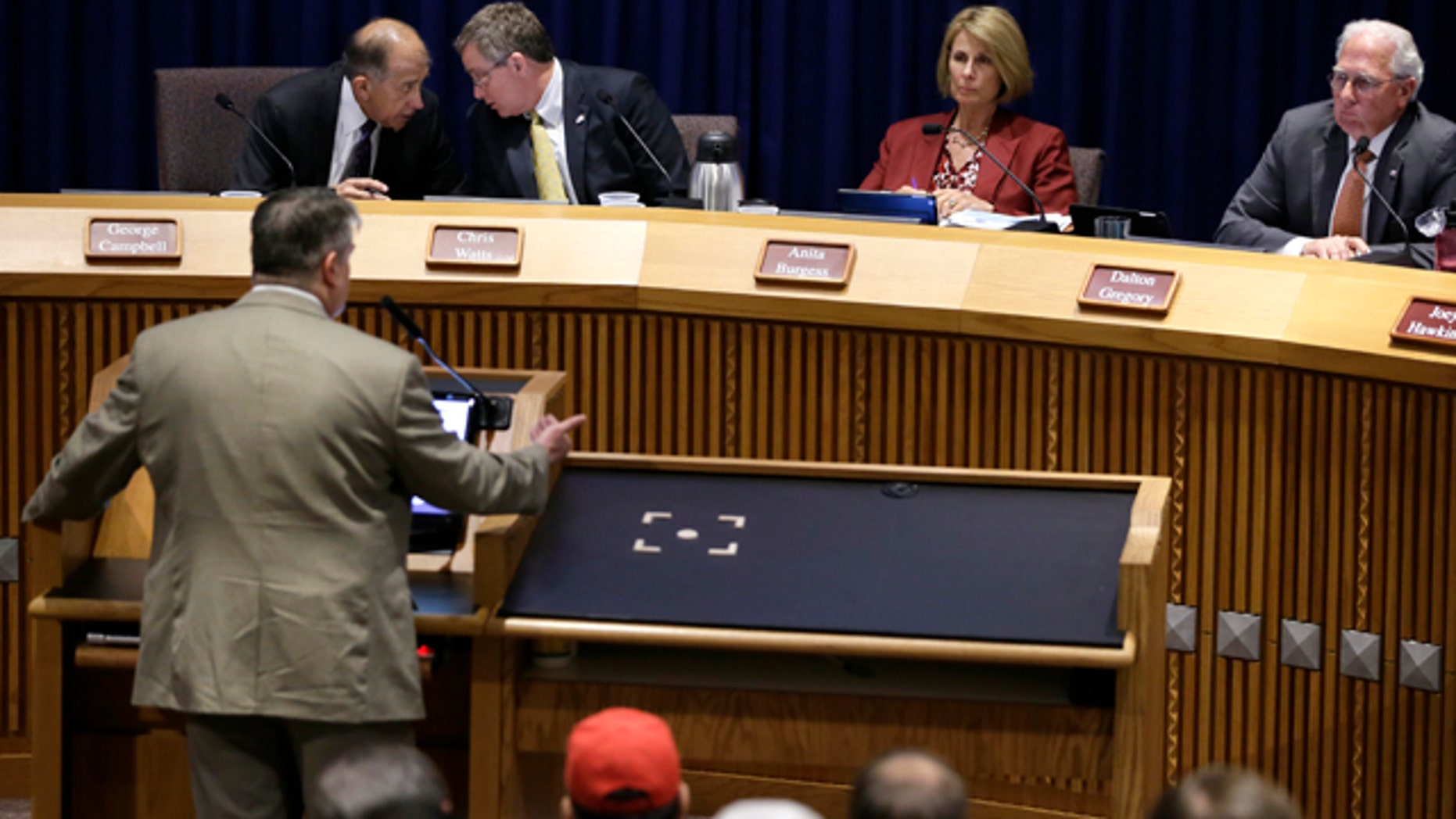 July 15, 2014: Denton, Texas Council member George Campbell, left rear, talks with Mayor Chris Watts as council members Anita Burgess and Dalton Gregory right, listen to former Texas Railroad Commission executive director John Tintara, at lectern, speak at a public hearing at City Hall. (AP Photo/Tony Gutierrez)