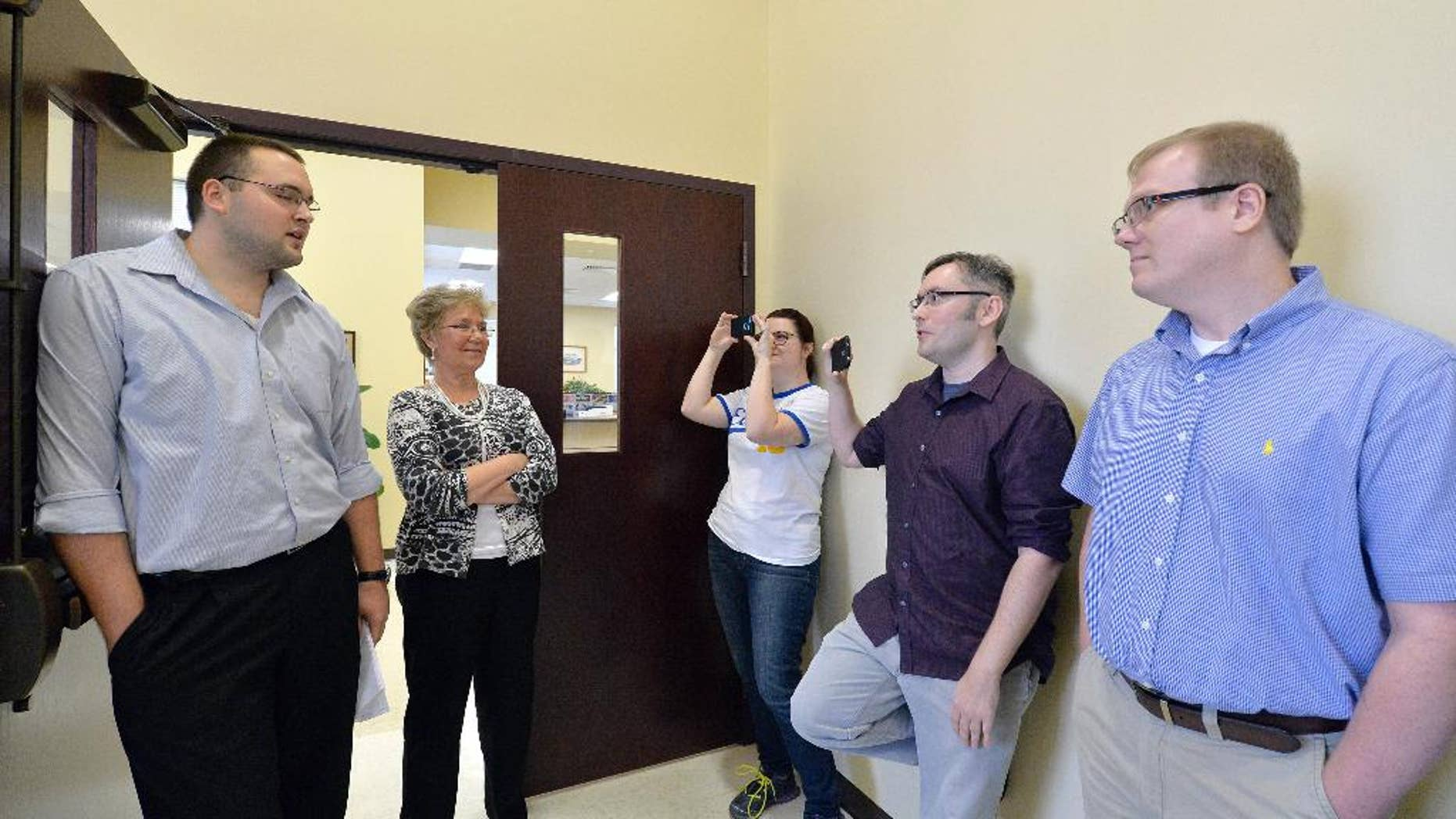 Rowan County clerks Nathan Davis, left, and Roberta Earley, second left, inform David Ermold, right, and David Moore, second from right, that the county clerk's office will not be issuing marriage licenses, in defiance of an order from a federal judge, in Morehead, Ky., Thursday, Aug. 13, 2015. Rowan County Clerk Kim Davis has already filed a notice of appeal and plans to request a stay on the ruling. (AP Photo/Timothy D. Easley)