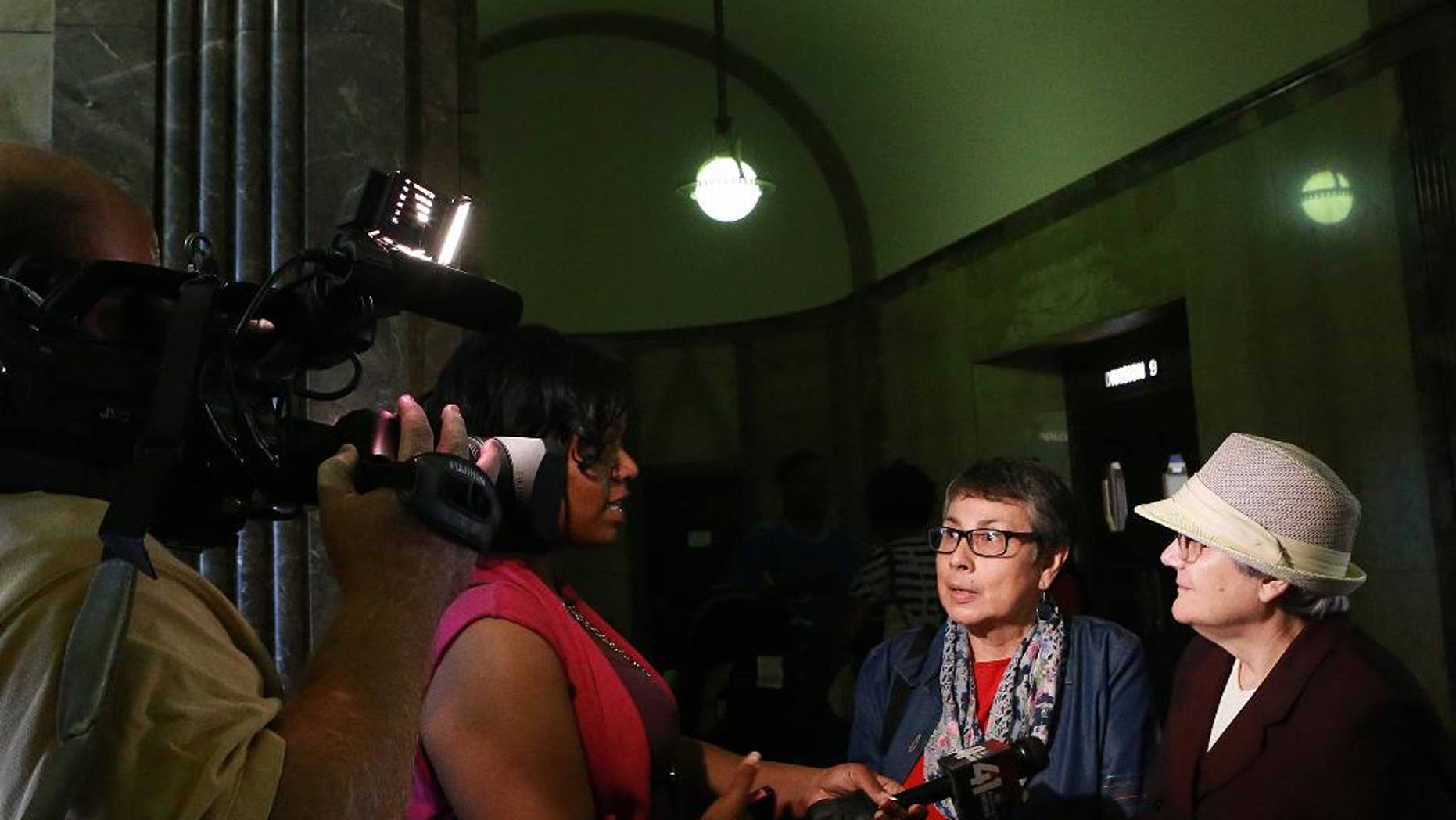 """FILE - In this Thursday, Sept. 25, 2014, file photo, same-sex couple Zuleyma Tang-Martinez, second from right, and Arlene Zarembka, right, of St. Louis, talk to news media in the Jackson County Courthouse in Kansas City, Mo. A judge struck down part of Missouri's gay marriage ban for the first time on Friday, Oct. 3, 2014, by ordering the state to recognize same-sex marriages legally performed in other states, saying state laws banning the unions single out gay couples """"for no logical reason."""" The ruling was made in a lawsuit filed by 10 same-sex couples who legally married outside the state, including Zarembka and Tang-Martinez. (AP Photo/St. Louis Post-Dispatch, Christian Gooden, Pool, File)"""